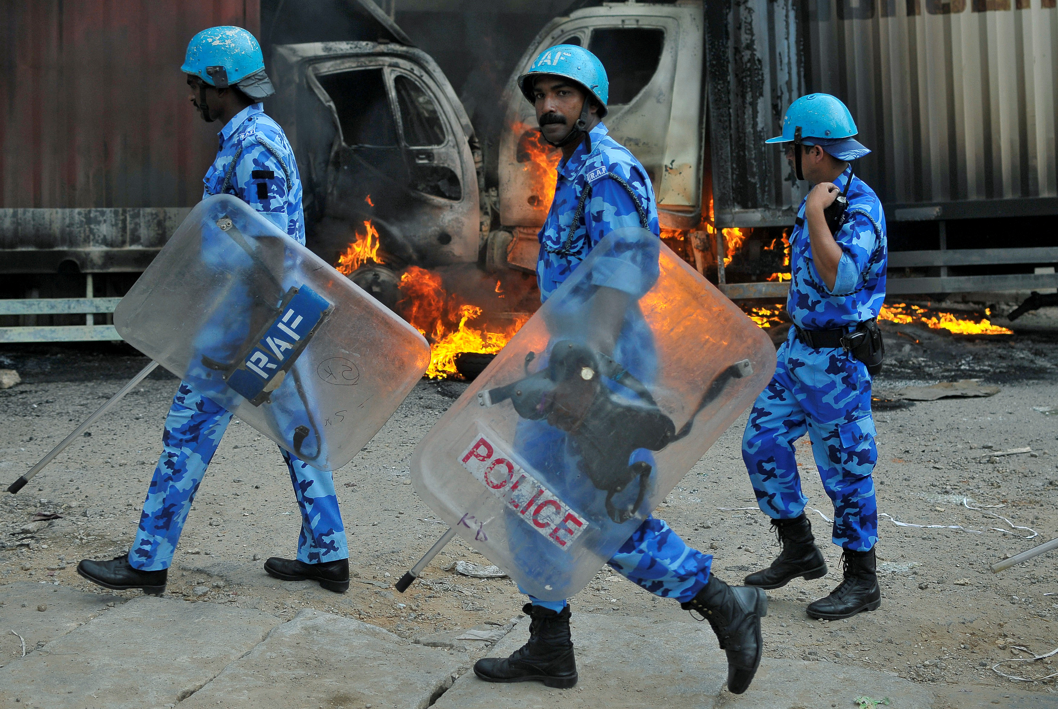 Security forces walk past lorries set on fire by protesters in Bangalore on Sept. 12, 2016, after the Supreme Court ordered the Indian state of Karnataka to release disputed water from the Cauvery river to the neighboring state of Tamil Nadu