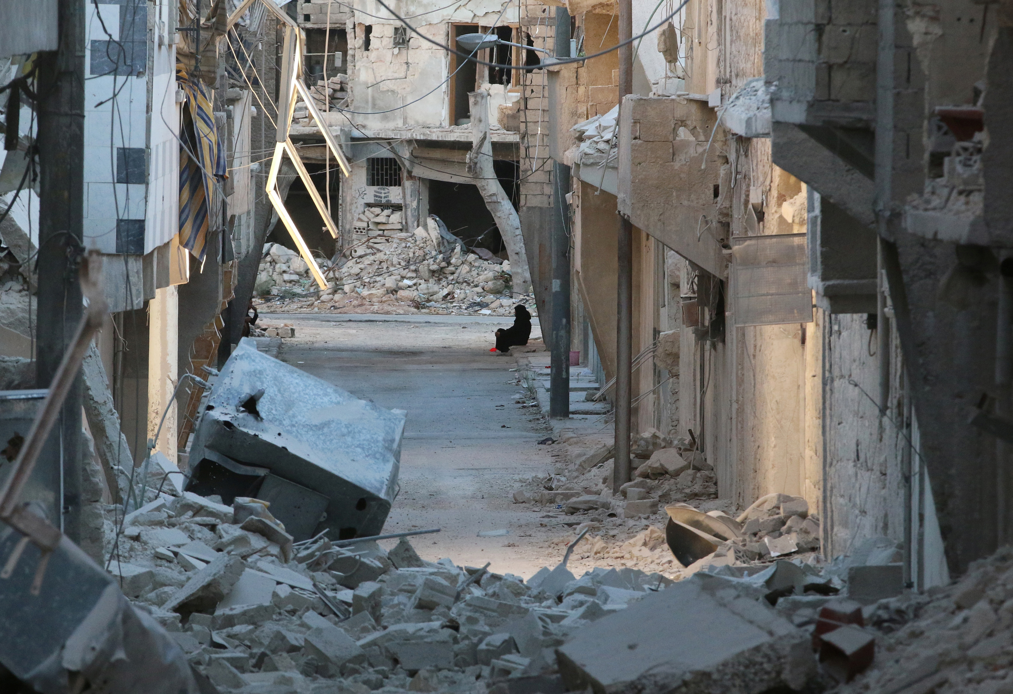 A woman sits amid damaged buildings in the rebel-held al-Myassar neighborhood of Aleppo, Syria, on Sept. 27, 2016