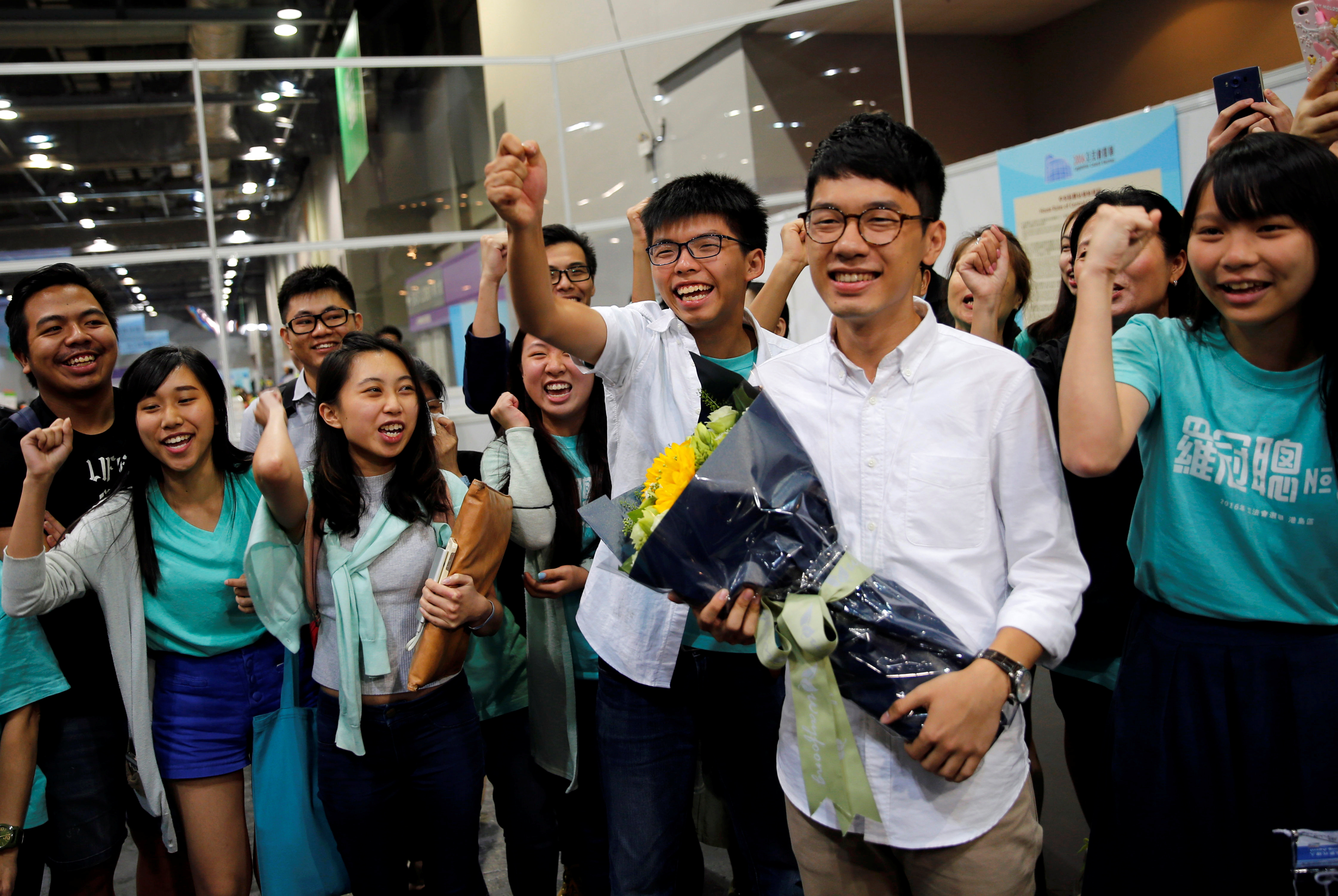 Student leader Joshua Wong, center, greets Demosistō's candidate Nathan Law, second right, as supporters share their joy Sept. 5, 2016, after Law won in the Legislative Council election in Hong Kong