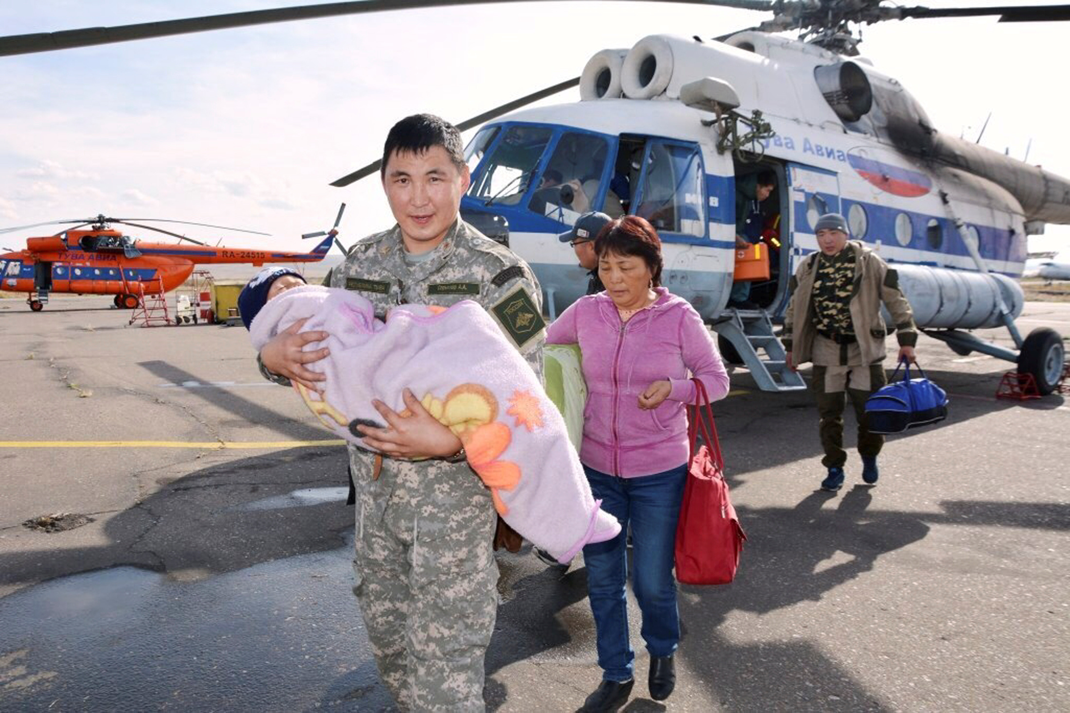 A photo released by the Russian Emergencies Ministry on Sept. 21, 2016, shows a rescuer carrying a three-year-old boy Tserin, who went missing in the Siberian Taiga area and was found three days later, at a landing site in Tyva region, Russia.