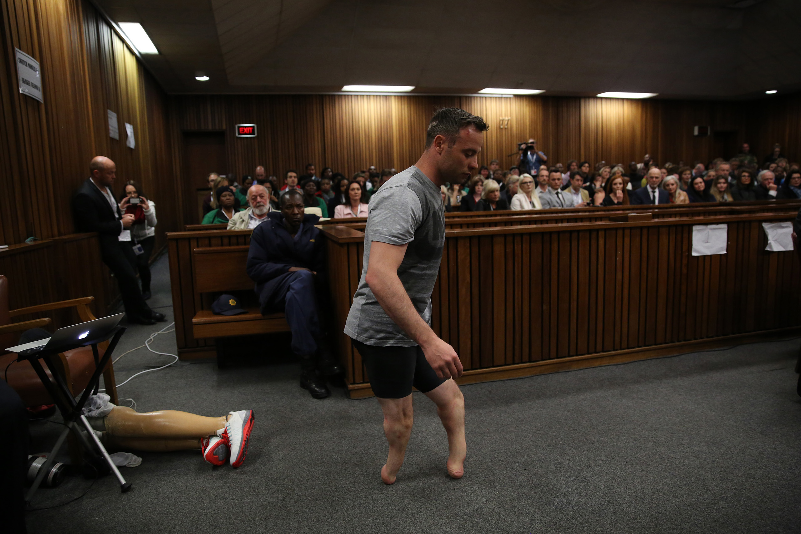 Paralympic gold medalist, Oscar Pistorius, prepares to walk across the courtroom without his prosthetic legs during the third day of his hearing at the Pretoria High Court for sentencing procedures in his murder trial in Pretoria on June 15, 2016.