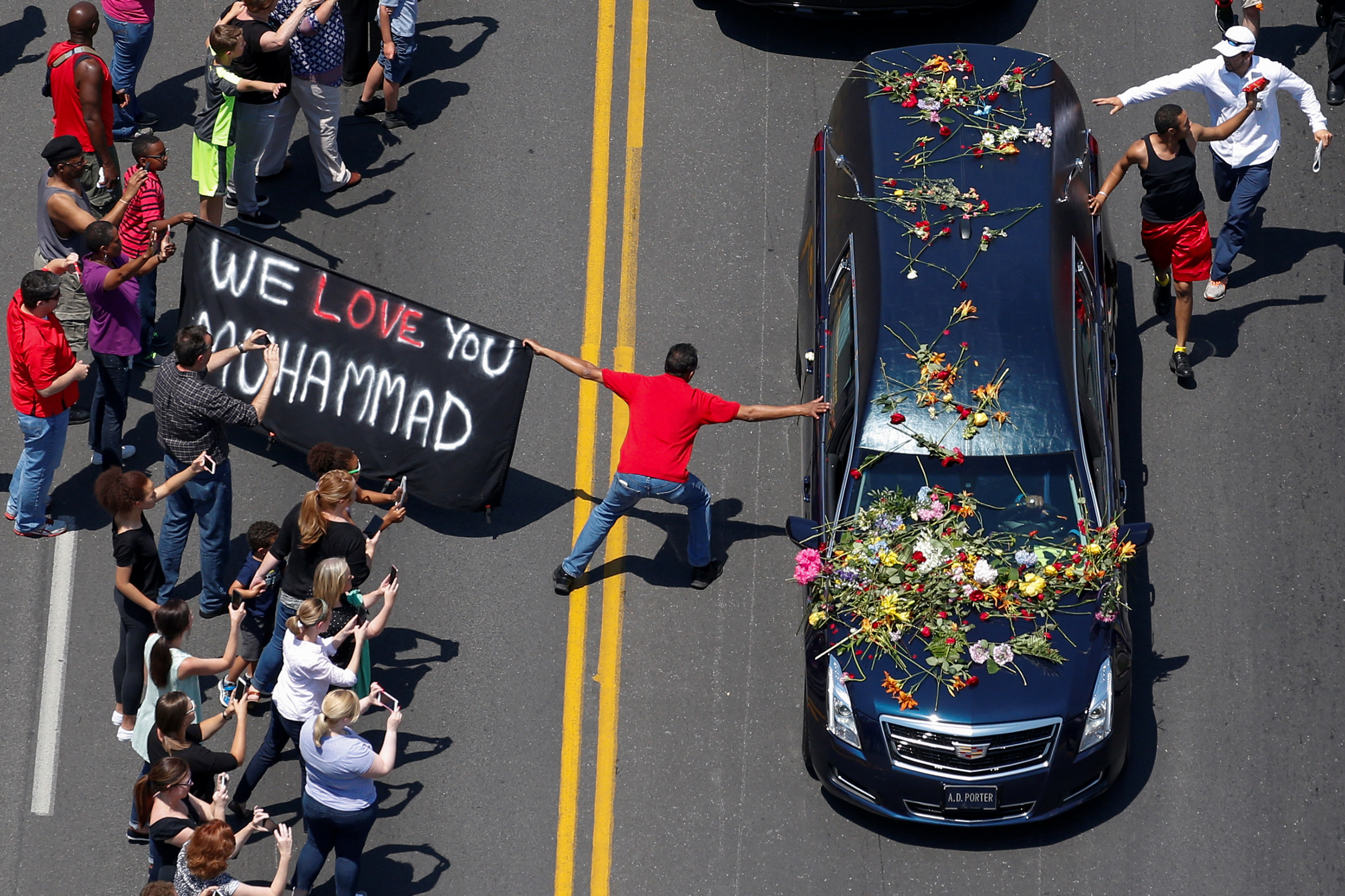 A banner stating  We Love You Muhammad  is displayed as well-wishers touch the hearse carrying the body of the late boxing champion Muhammad Ali during his funeral procession through Louisville, Kentucky, June 10, 2016.