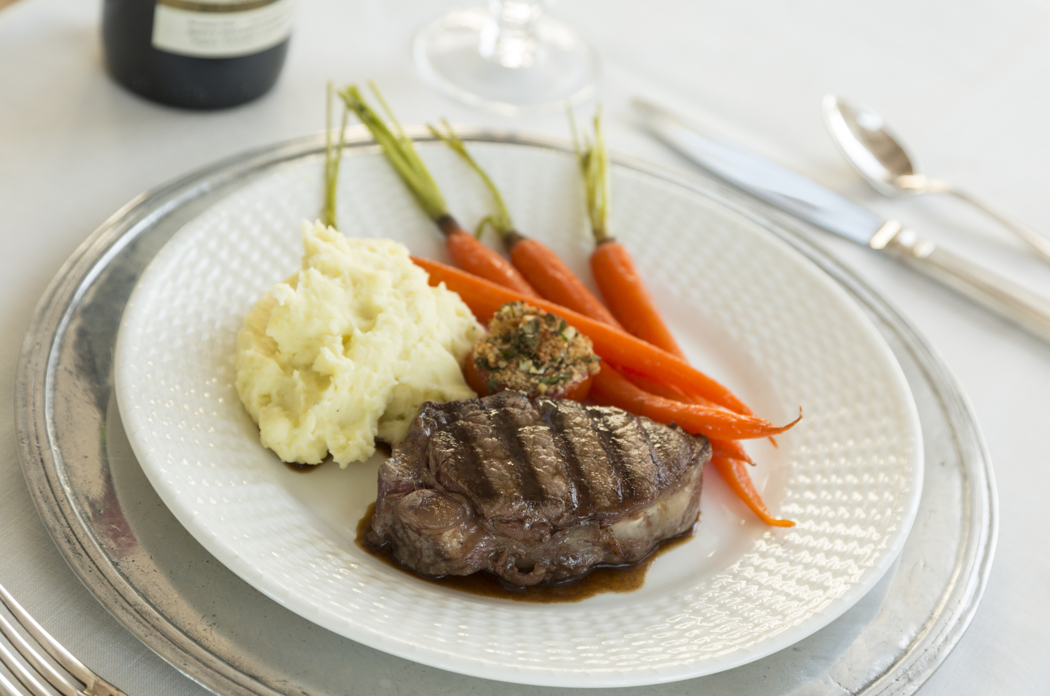Beef steak with carrots, mashed potatoes and stuffed tomato