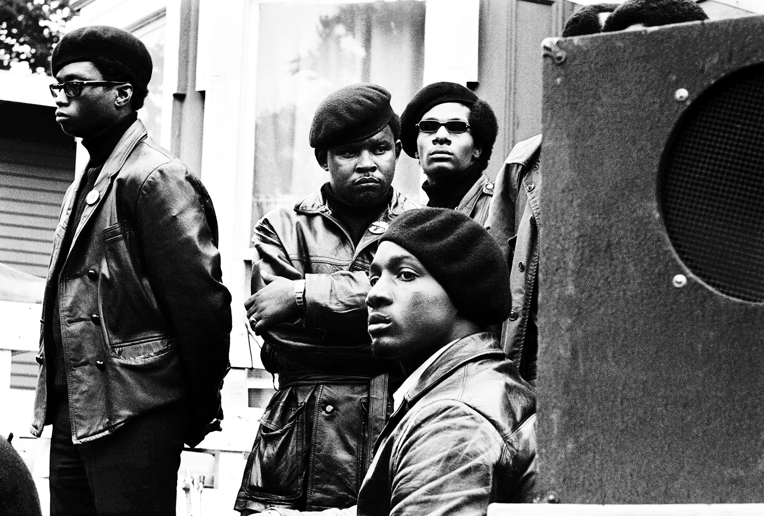 Panthers stand just off stage at a Free Huey rally in Defermery Park, Oakland 1968.  Che Brooks (arms folded) was a San Francisco Panther who went to San Quentin State Prison and started the prison chapter.