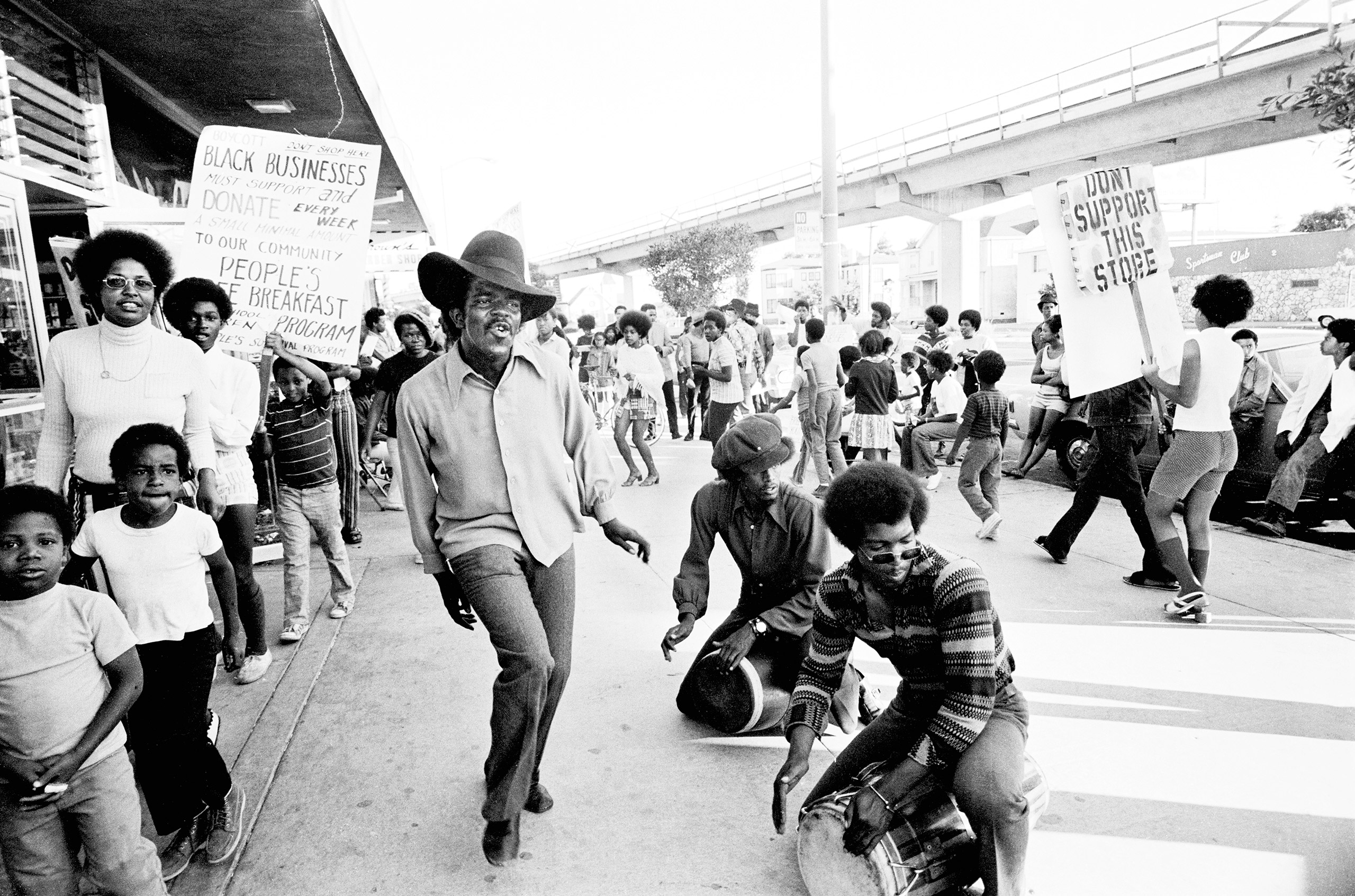 The Lumpen, the Panthers' singing group, performs at the boycott of Bill's Liquors, Oakland, 1971. Clark Bailey, known as Santa Rita, is dancing. Michael Torrence (front) and James Mott (back) are drumming.