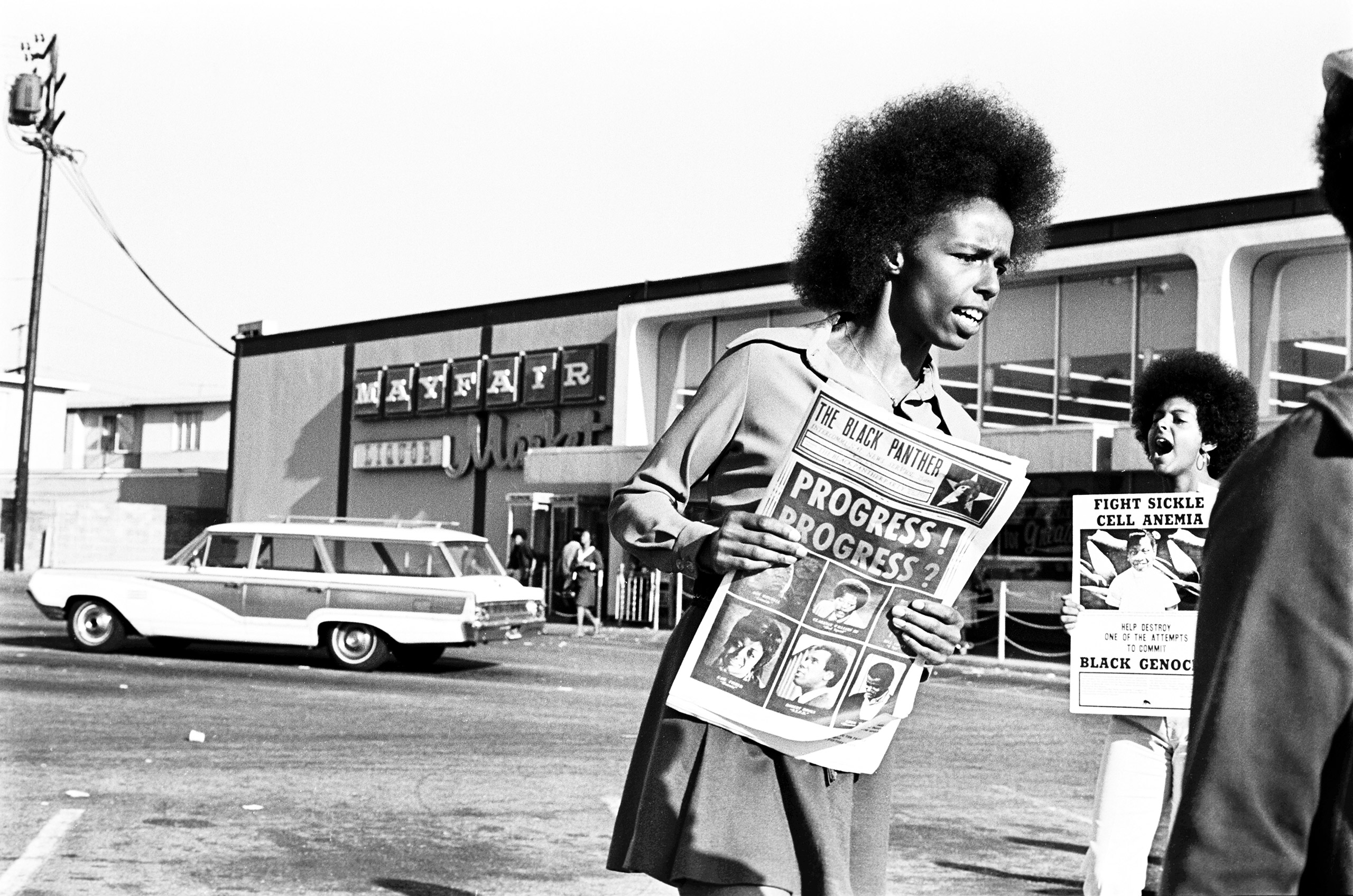 Gloria Abernathy selling papers at the Mayfair supermarket boycott, Oakland, 1971. Tamara Lacey is in the background holding a poster.