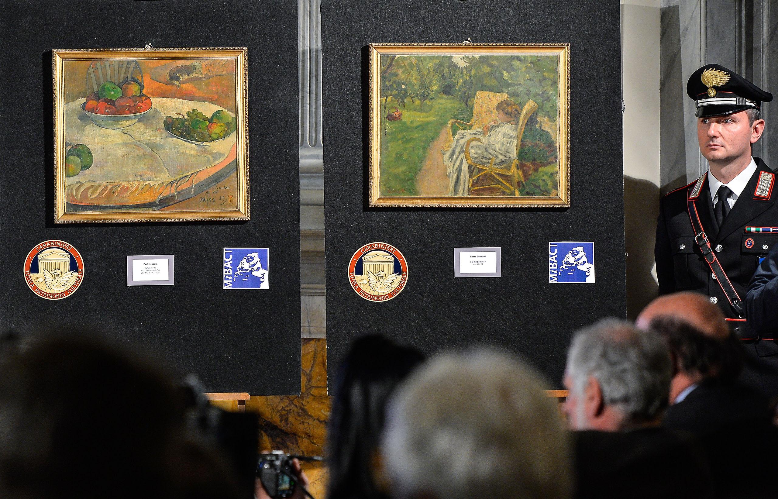 A Carabinieri stands next to the two paintings stolen in London in the 1970s,  Fruits sur une table ou nature morte au petit chien  by French artist Paul Gauguin and  La femme aux deux fauteuils  by Pierre Bonnard, on April 2, 2014.