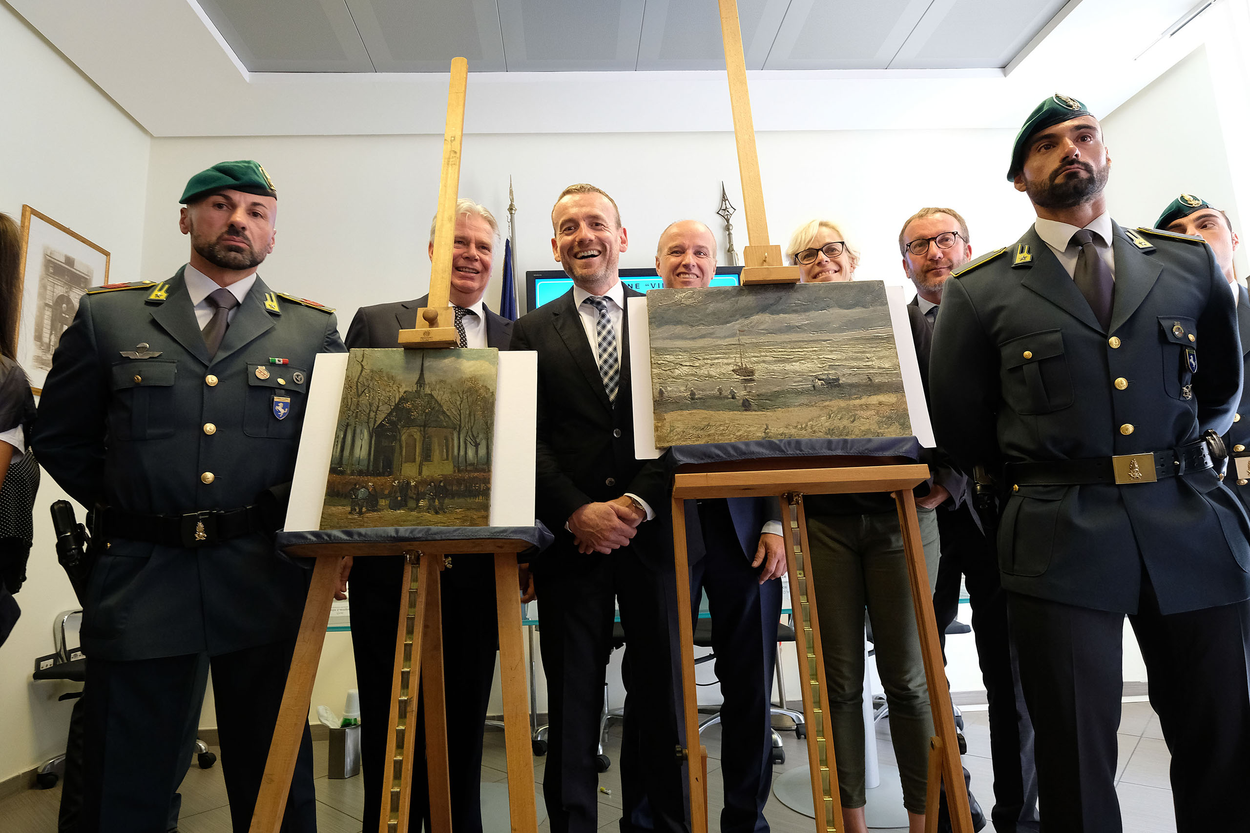 Axel Ruger, Director of the Van Gogh museum, poses next to  Congregation Leaving the Reformed Church in Nuenen  (L) and  The Beach At Scheveningen During A Storm  (R) by Vincent van Gogh. The two Van Gogh paintings were stolen in Amsterdam 14 years ago and recently recovered by organized crime investigators in Italy, on Sept. 30, 2016.