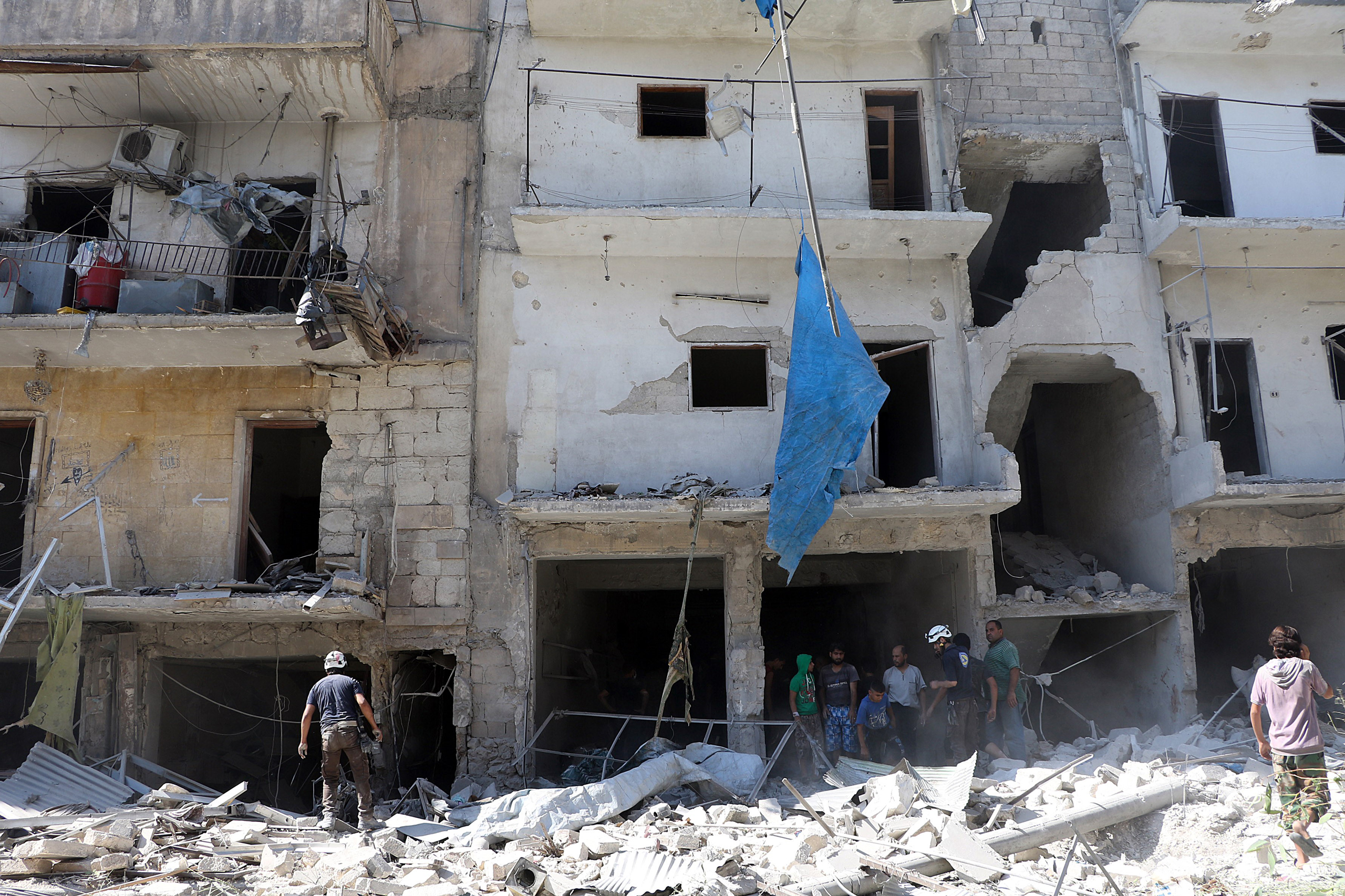 Search and rescue team members inspect the debris of buildings after Russian army aircrafts hit residential areas in the Sukari district of Aleppo, Syria, on Sept. 7, 2016.