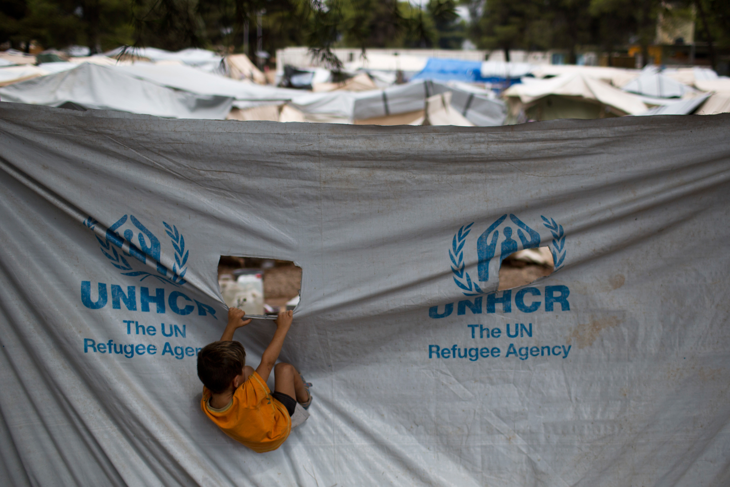 A child play in front of a UNHCR plastic sheet at Ritsona refugee camp, north of Athens, on Sept. 8, 2016.