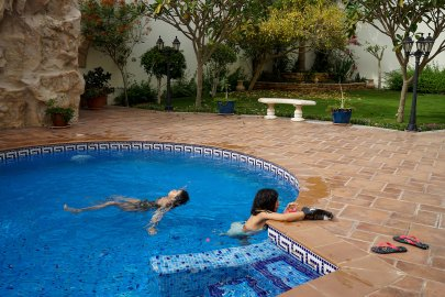 "The photographer's daughters, Sura and Yara, swim in a pool at a friend's home in Dhahran, Saudi Arabia, April 2016. ""They lay there, free, and careless,"" Alsultan says. ""There's no public pools for women, neither is there any beach spaces for women only. Only privately owned or very expensive clubs that is not available to Saudis."""