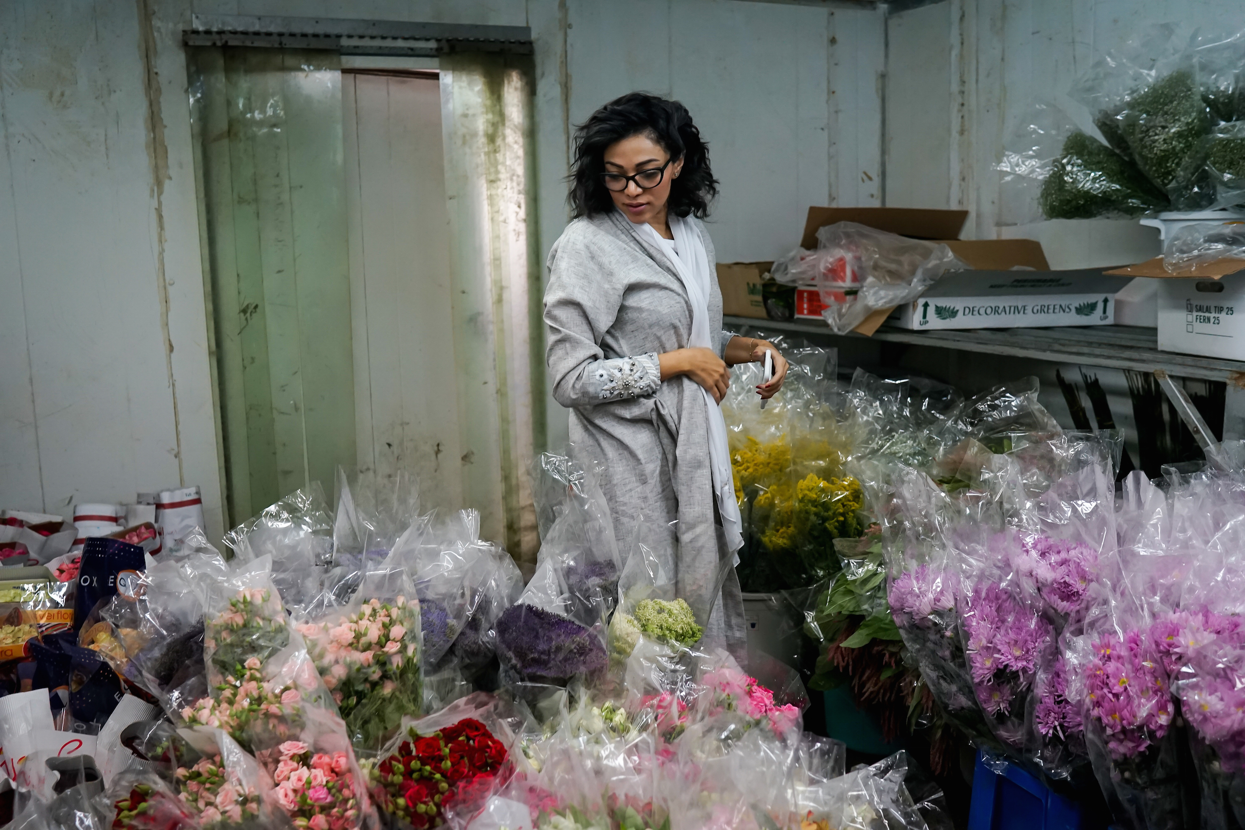 Ghadeer, a well-known wedding planner in Saudi Arabia, chooses flowers for an upcoming event at a florist in Jeddah, May 2016. A friend of the photographer, she says she has never been married or in love.