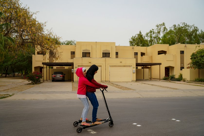 The photographer's daughters, Sura and Yara, ride a scooter around the block of their neighborhood in Jubail Industrial City, April 2016. As they appear young, Alsultan says, no one will harass them.