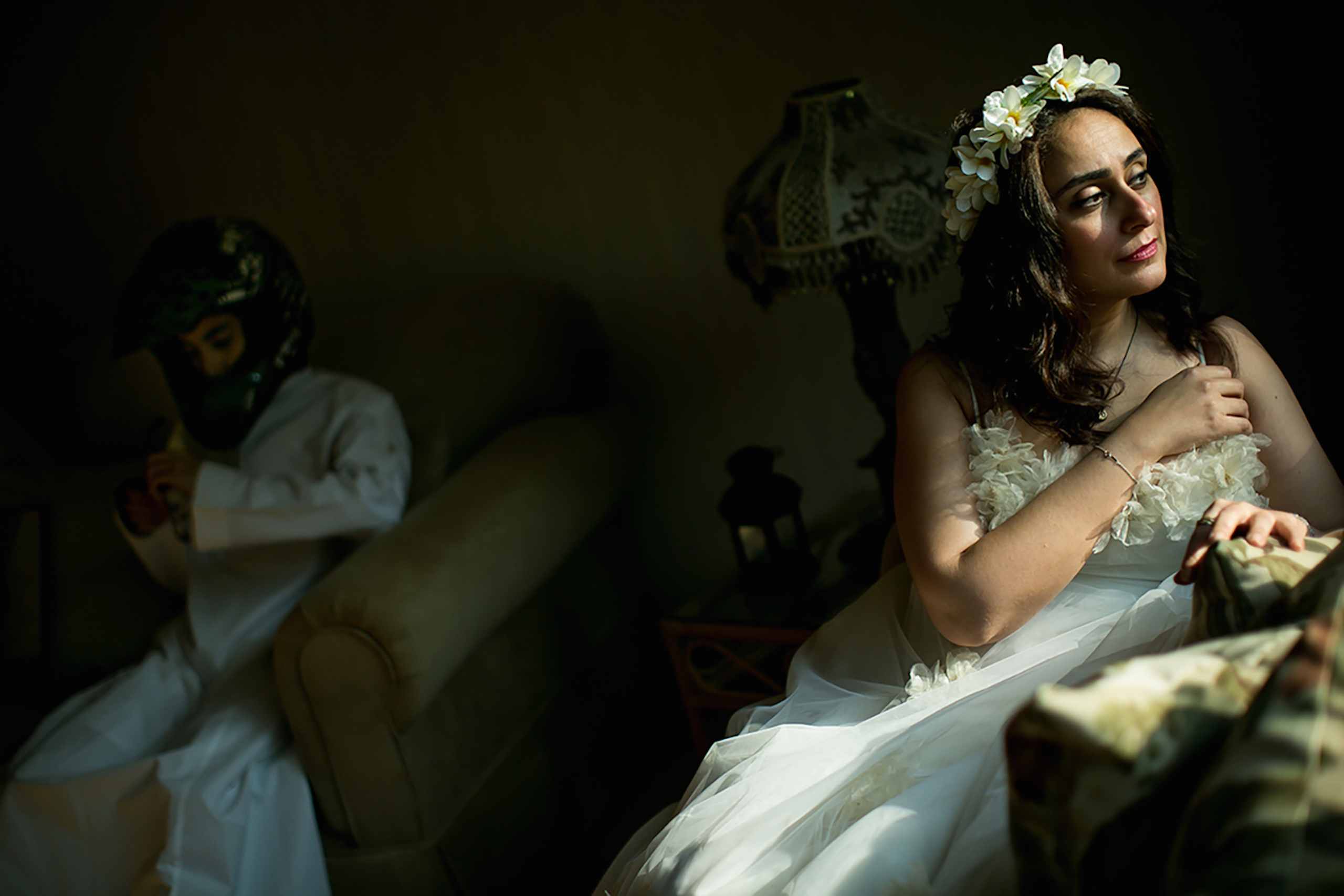 Mai sits in her wedding dress that she wore 15 years ago while her son sits in the background in Jeddah, October 2015.  I married my college classmate in dental school. Sharing two children and a happy marriage, we finally decided to buy our dream house. Two days before signing the lease, he died in a motorcycle accident. Then, my father died. I was legally required to have a male guardian. I now wait for my son to turn 16 to take that role. Until then, my half brother decides on my behalf.