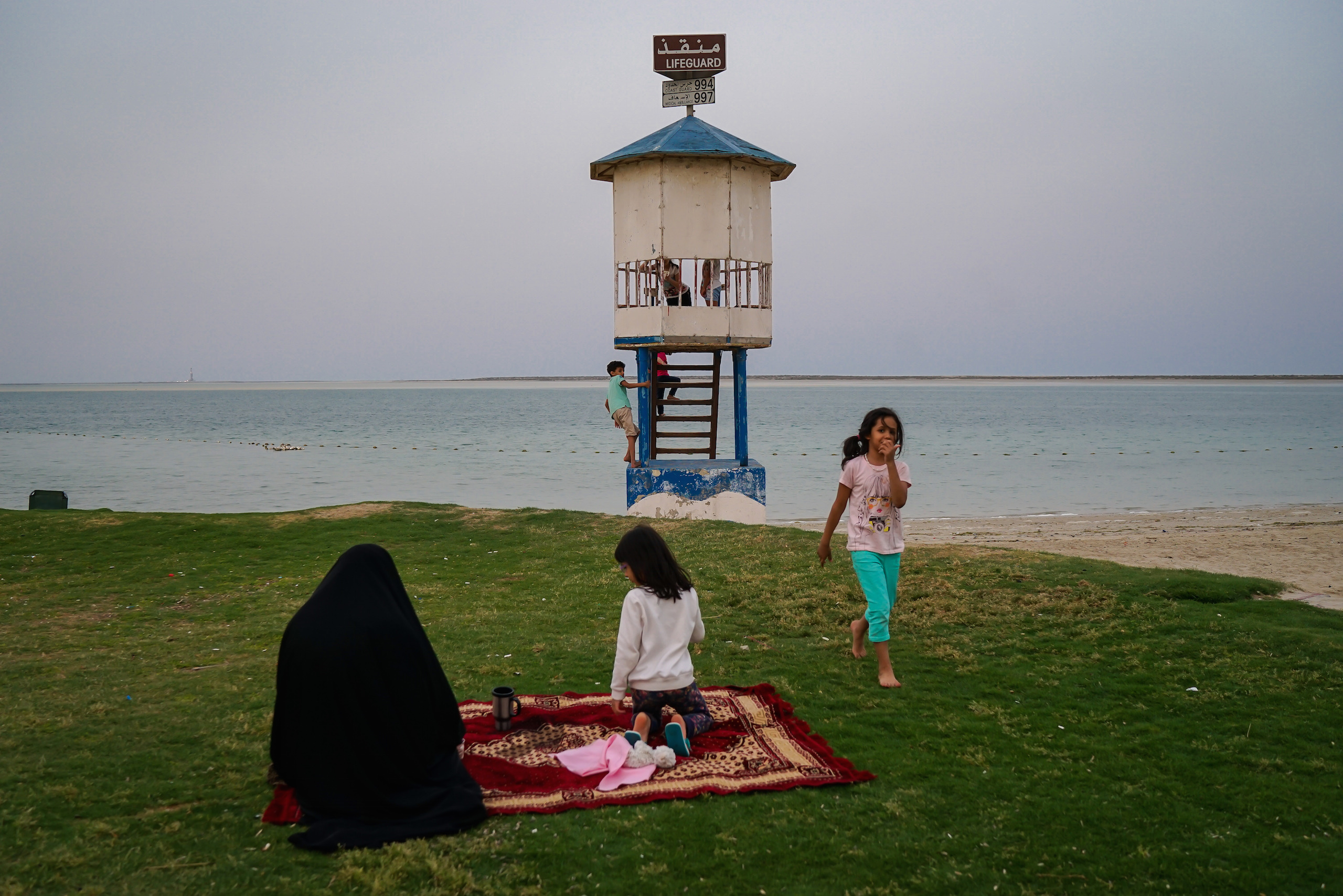 A six-year-old girl walks out of the lifeguard booth full of kids, but no lifeguard, in Jubail Industrial City, April 2016.  Why are you taking a picture?  she asked the photographer, who replied,  perhaps because these images preserve time?  Her father was standing nearby. The girl then said,  I will remember that I can't swim here, but my brother can,  before returning to play with other children.