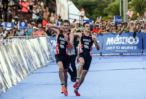 British athlete Alistair Brownlee (L) helps his brother Jonathan Brownlee (R) before crossing the line in second and third place during the ITU World Triathlon Championships 2016 in Cozumel, Quintana Roo, Mexico on September 18, 2016.