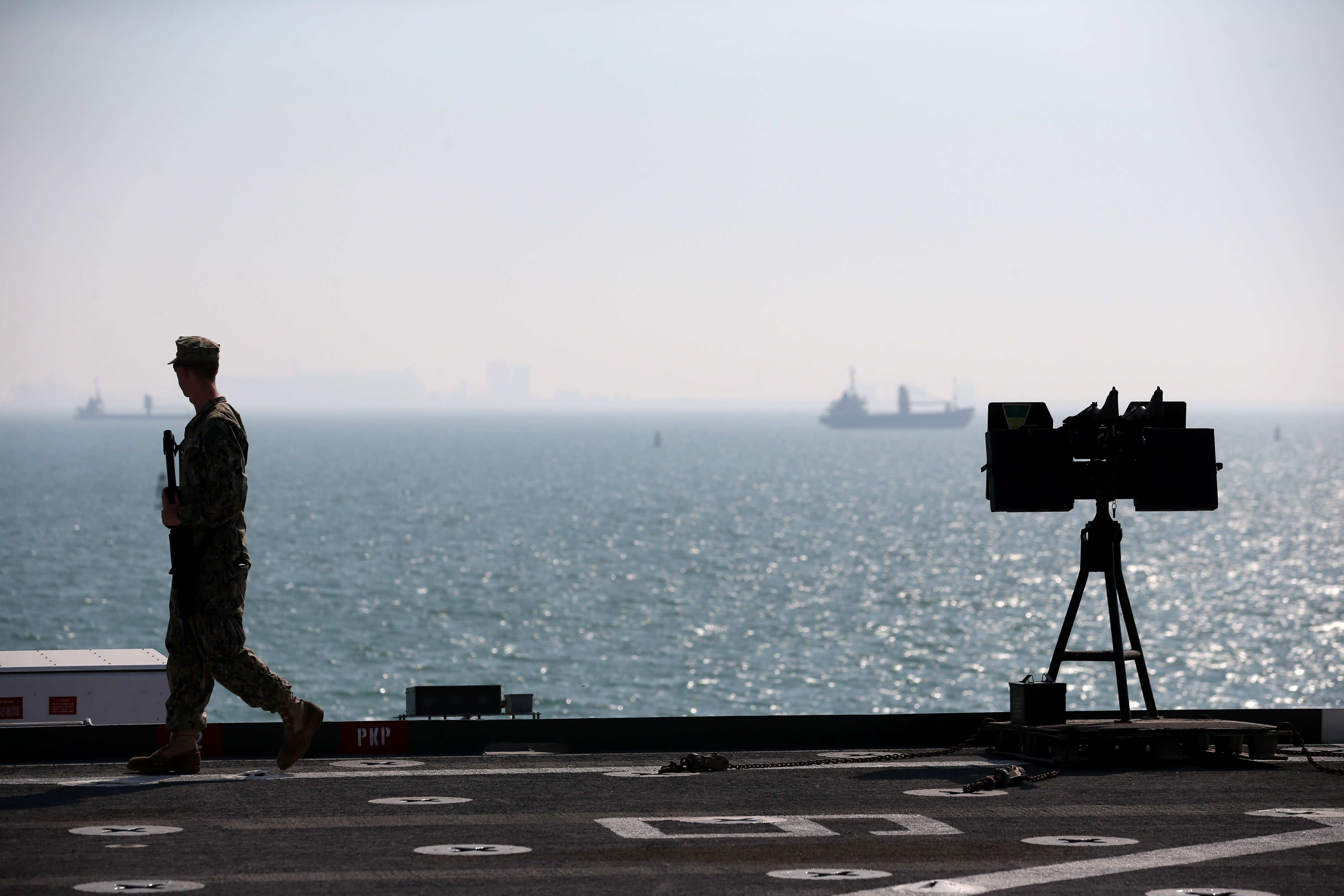 A Military guard patrols the deck of the USS Ponce where US Secretary of State Chuck Hagel was touring, on Dec. 6, 2013 in Manama, Bahrain.