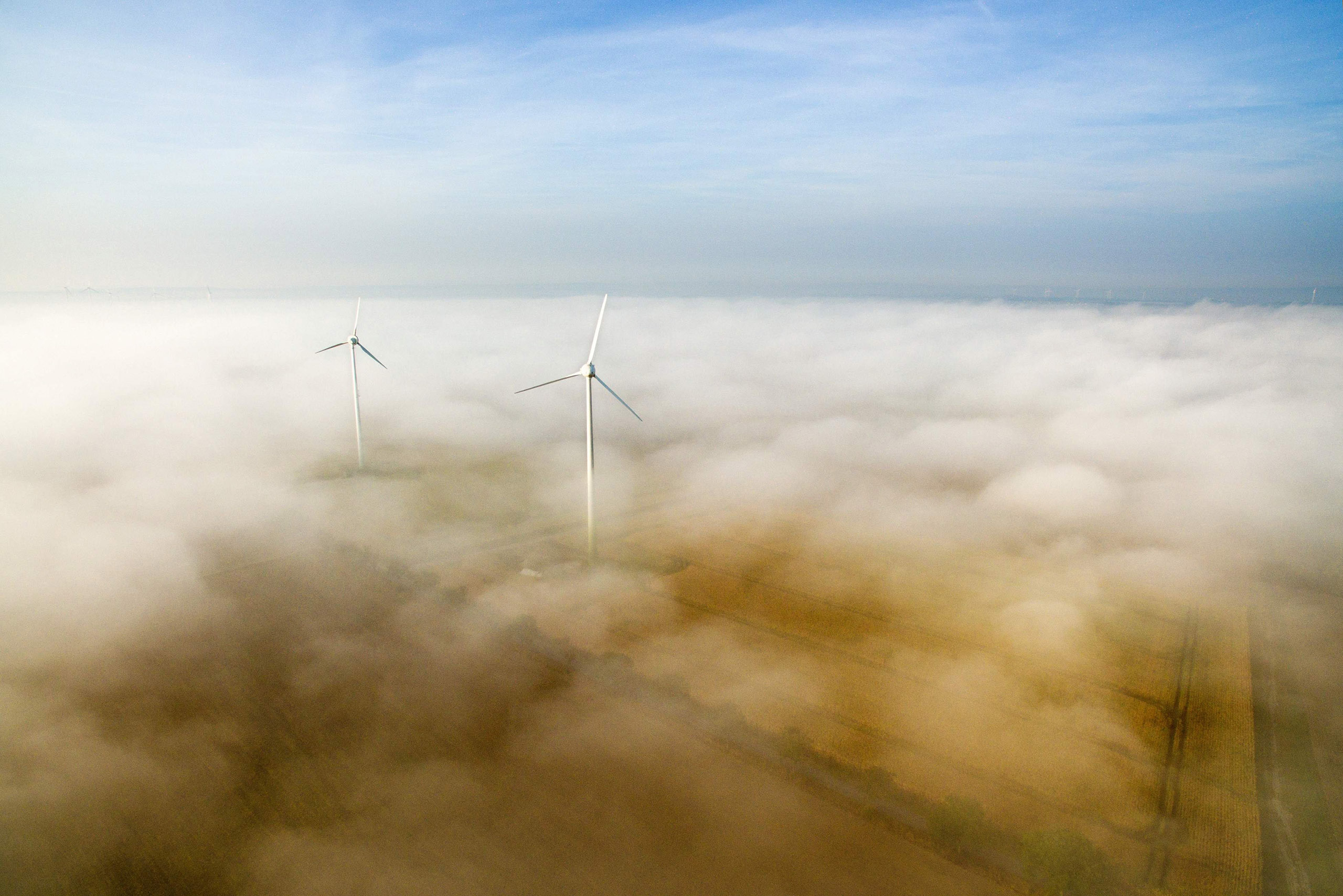 Windmills are seen through the morning mist rising from a field in Sehnde near Hanover, northern Germany, on Sept. 22, 2016.