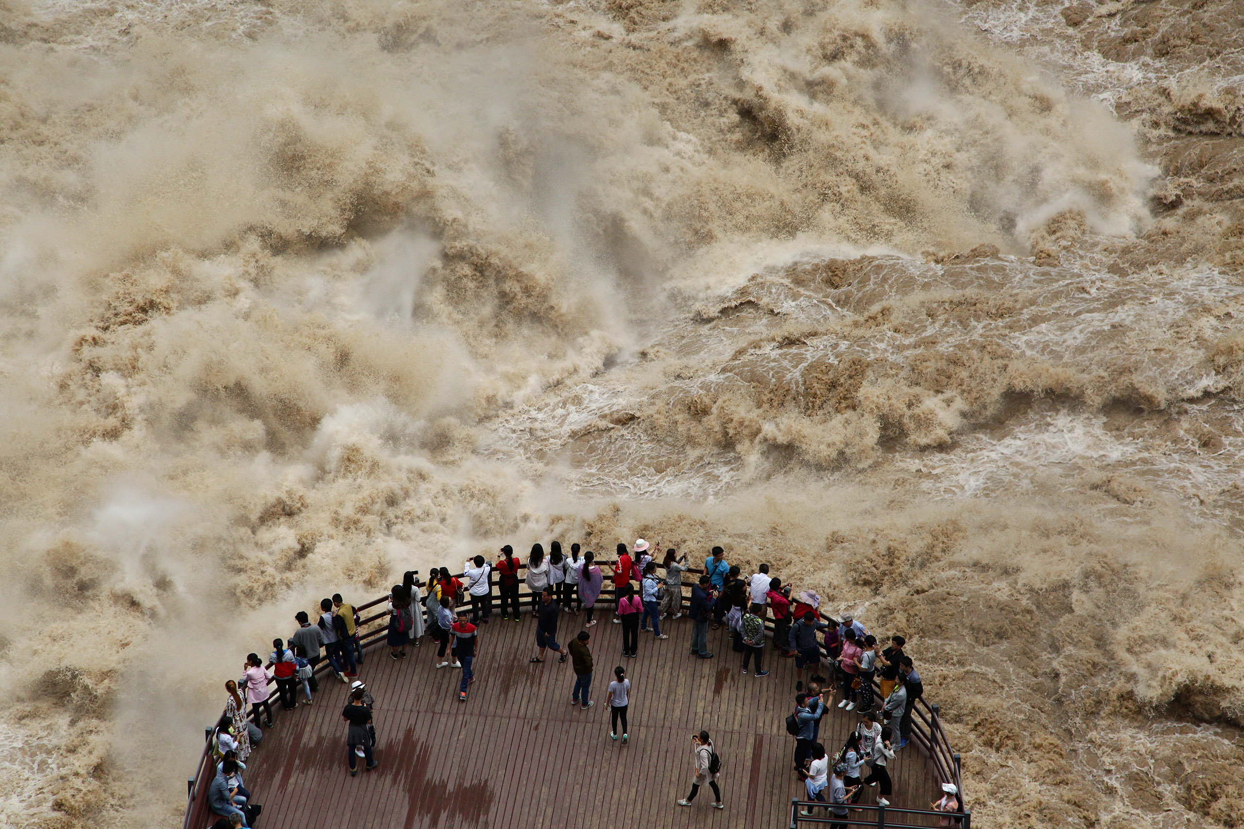 People watch the flooded Jinsha River at a sightseeing platform in Tiger Leaping Gorge, in Diqing, Yunnan Province, China, on July 15, 2016.