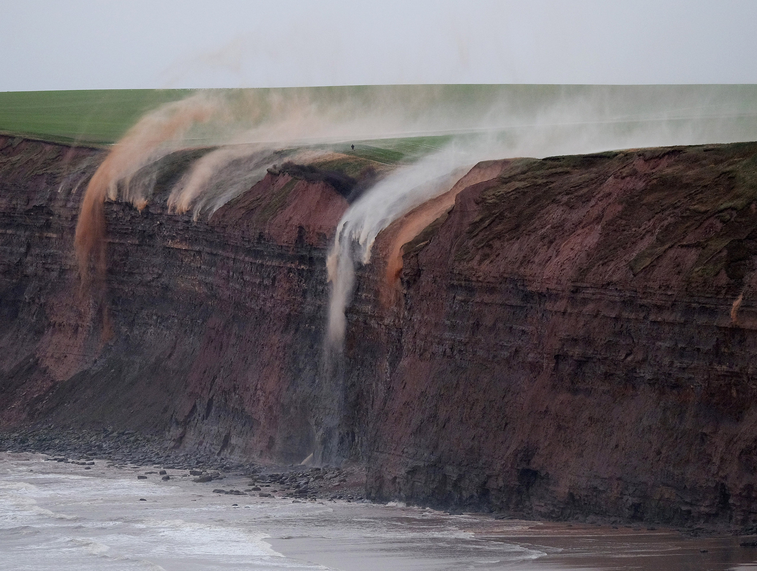 High winds blowing off the North Sea force rainwater from fields back over the cliff edge at Huntcliff in Saltburn-by-the-Sea, England, on Jan. 14, 2016.