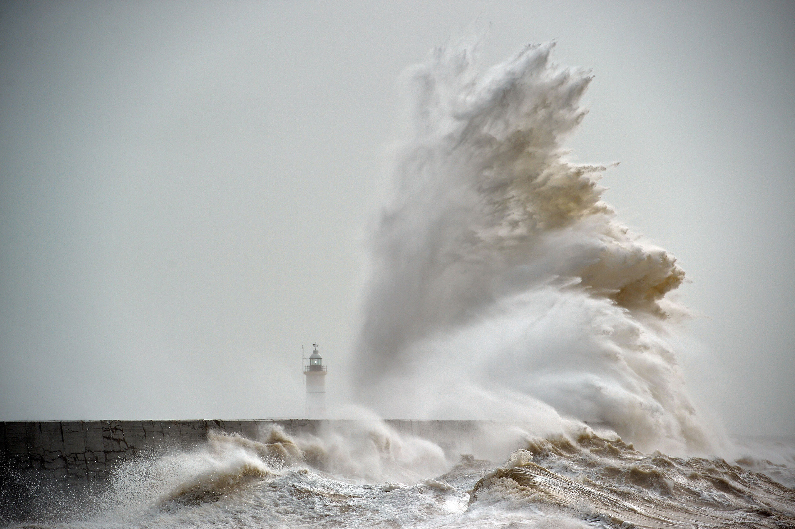 Waves crash over Newhaven Lighthouse on the south coast of England on Feb. 8, 2016.