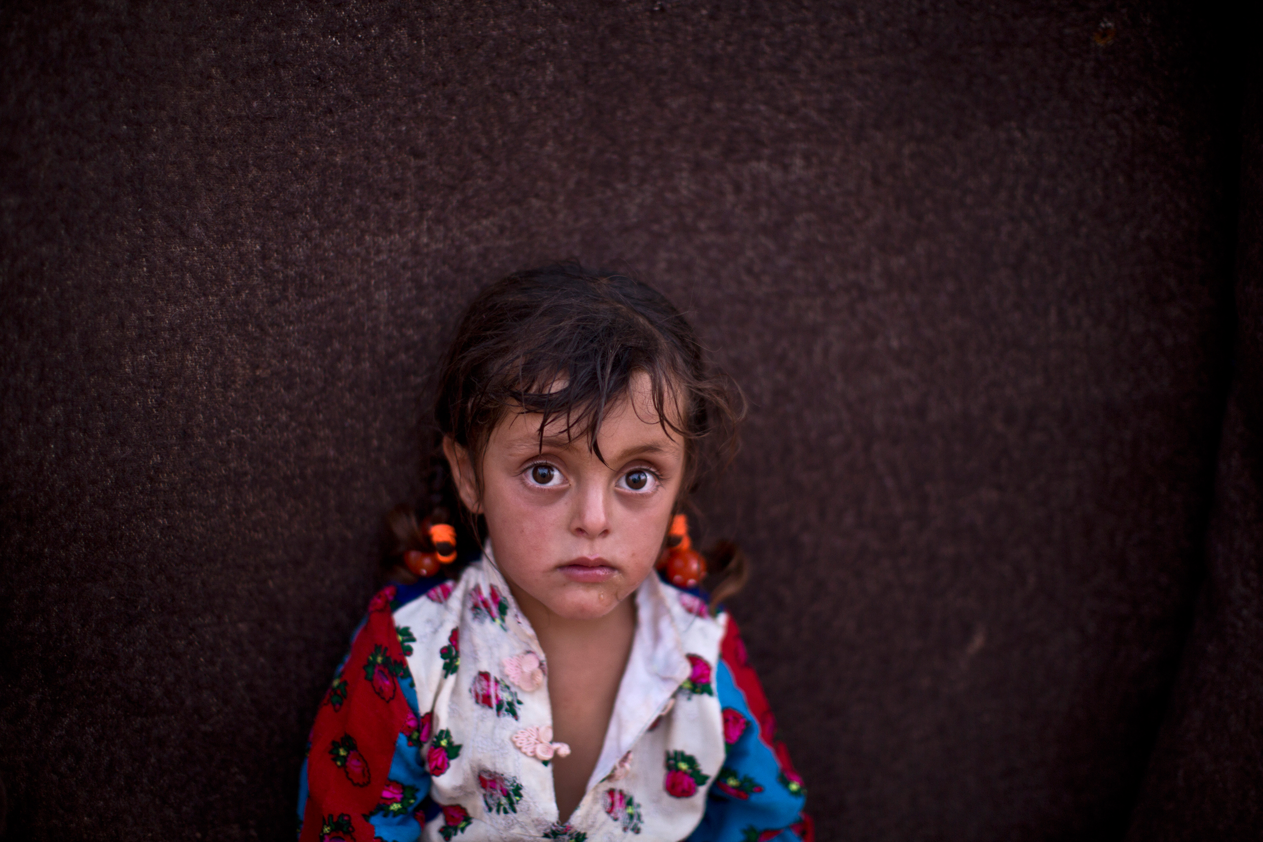 Zahra Mahmoud, four, sits in front of her family's makeshift home at an informal tented settlement near the Syrian border on the outskirts of Mafraq, Jordan, on Aug. 19, 2015.