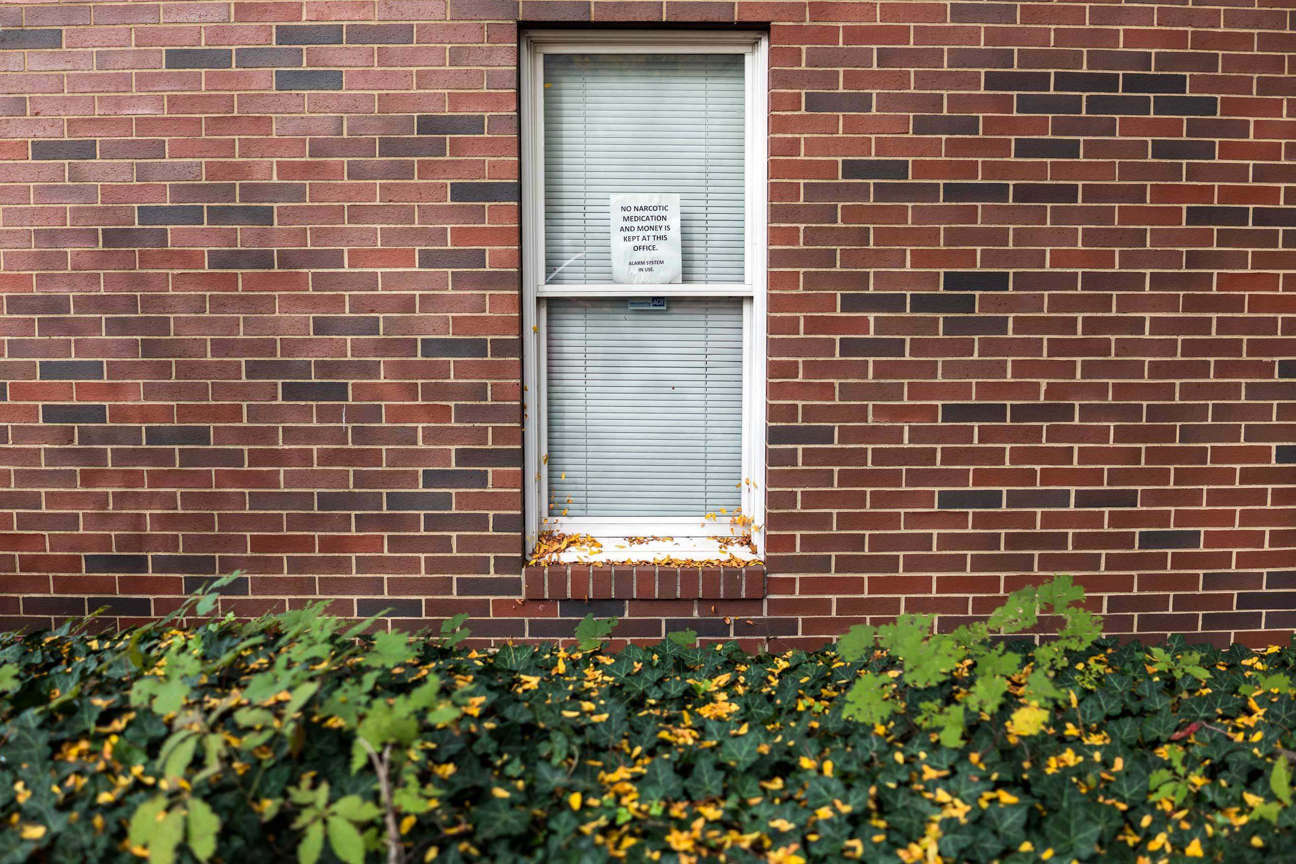 """A sign hangs in the window of a small medical clinic in downtown East Liverpool, Ohio, on Oct. 8, 2016. """"No Narcotic medication and money is kept at this office,"""" it reads. Stores and shops are frequently burglarized by addicts, according to police."""
