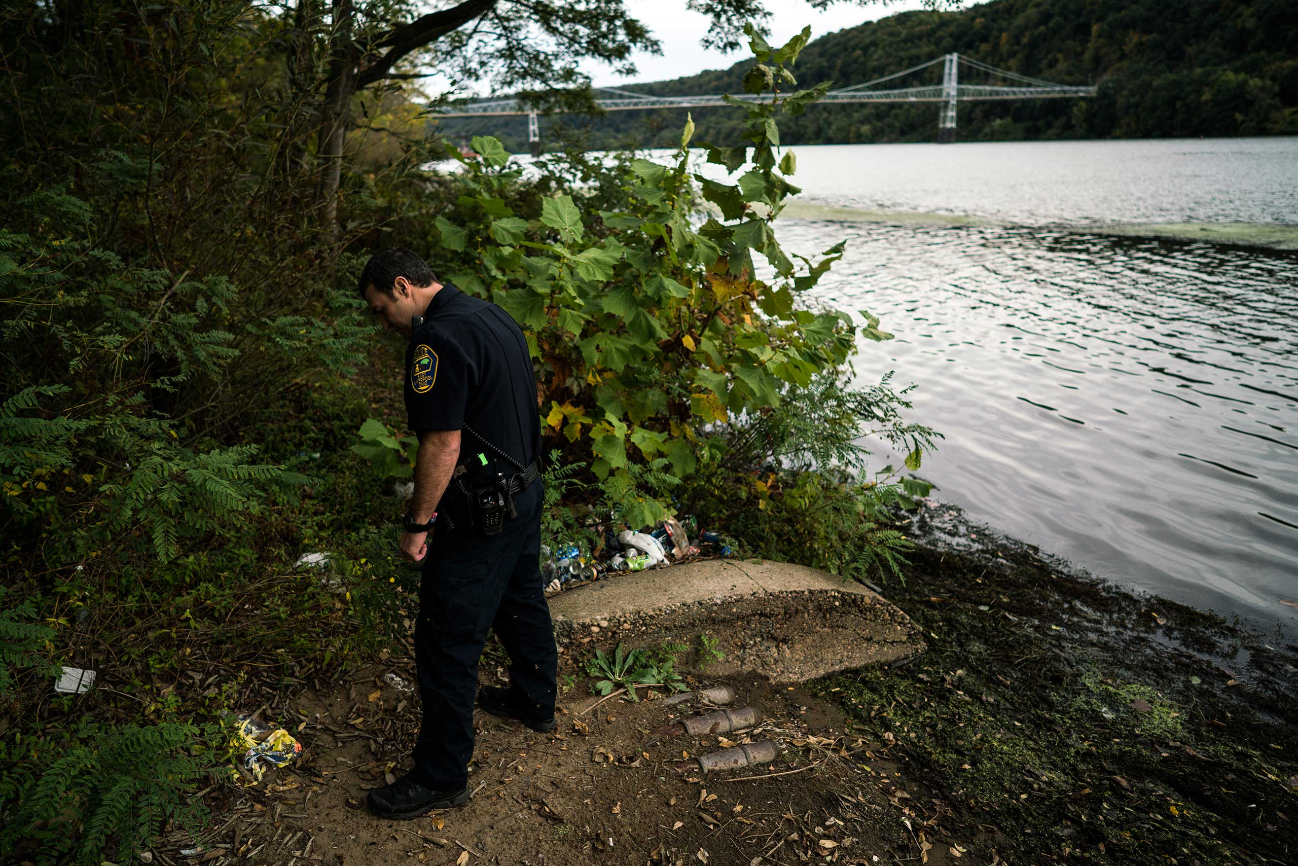 A patrolman searches for syringes and abandoned drug paraphernalia along the shore of the Ohio River in East Liverpool, Ohio, on Oct. 8, 2016.