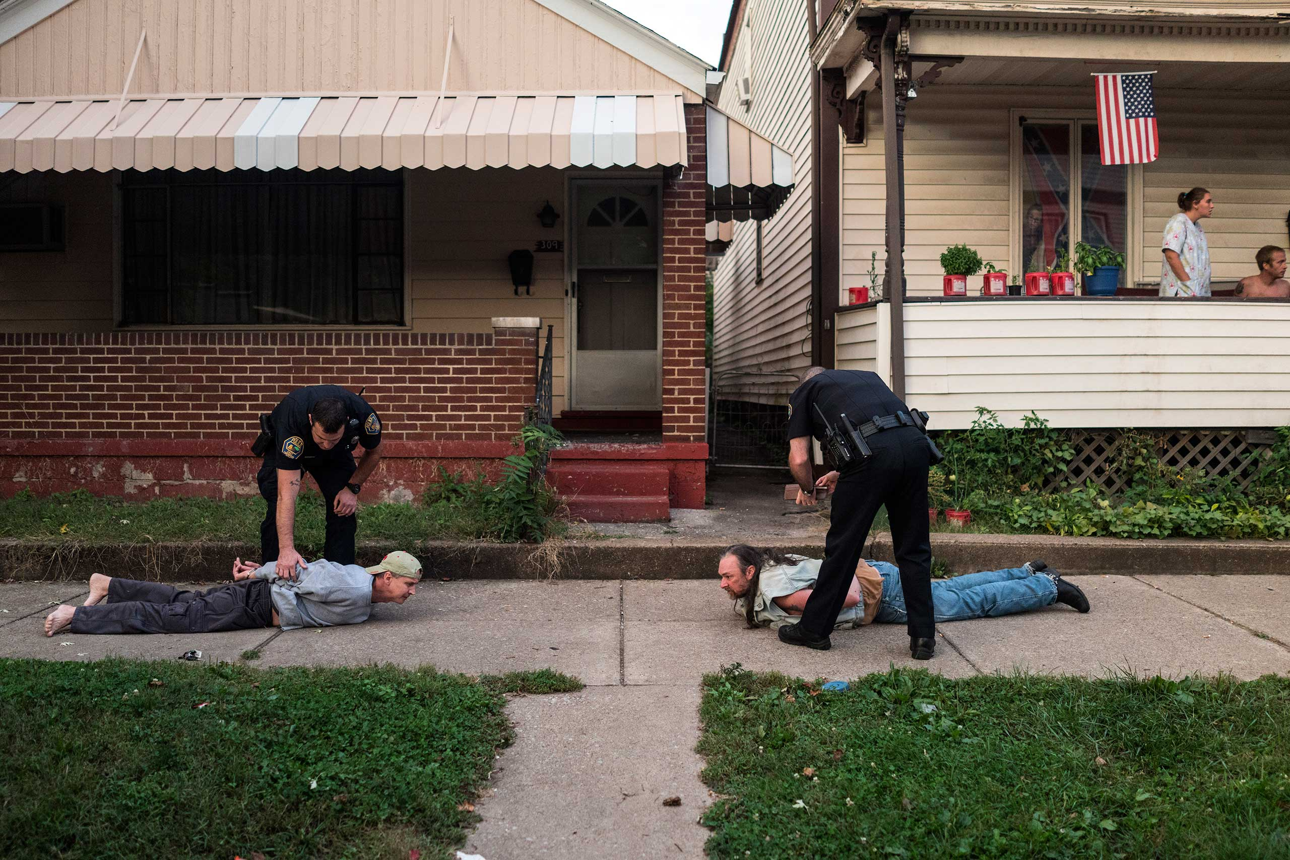 Officers arrest two men after an apparent an assault as neighbors watch in East Liverpool, Ohio, on Oct. 8, 2016.