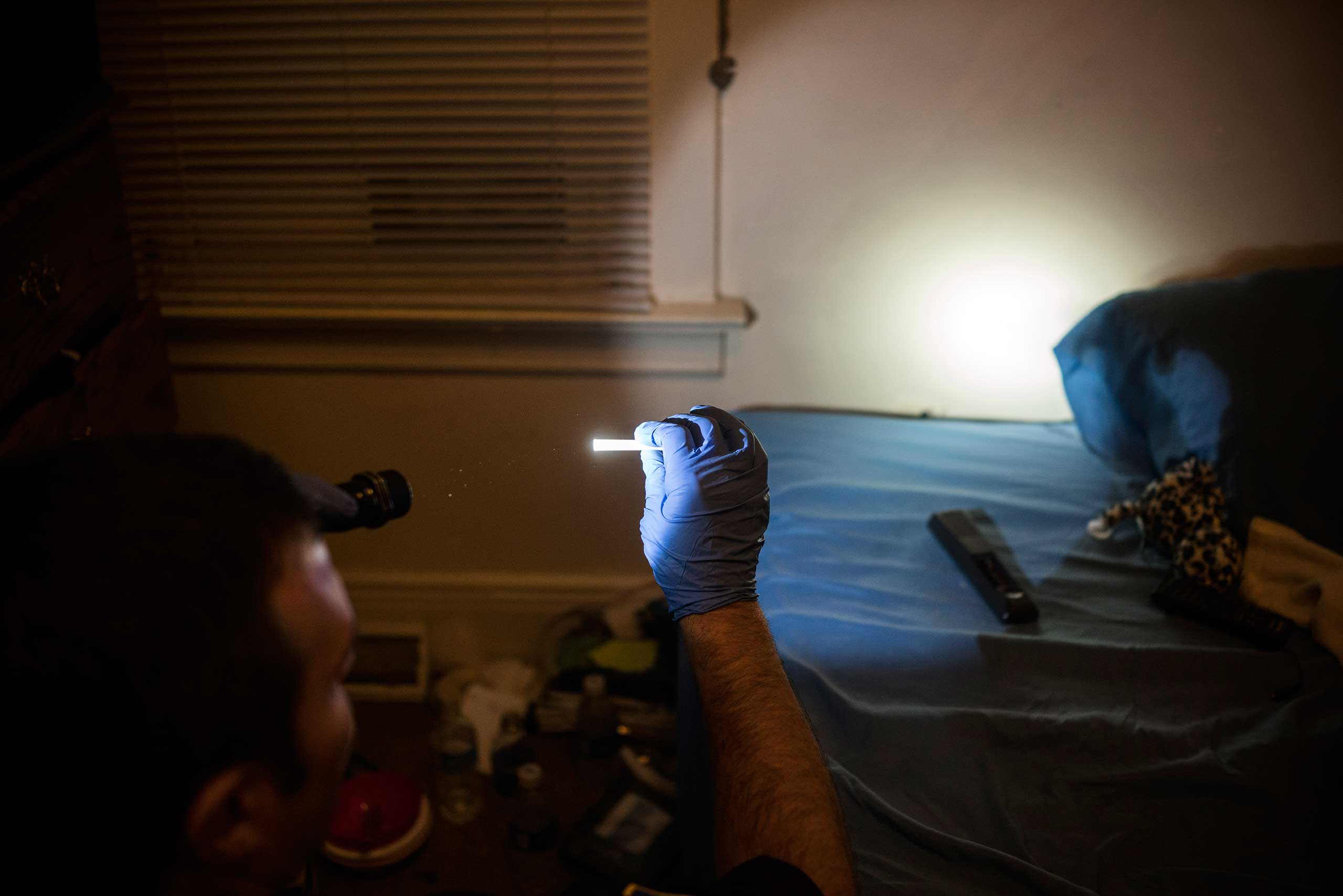 """A police officer holds up drug paraphernalia after searching through a teenager's room in East Liverpool, Ohio, on Oct. 8, 2016. The teen's mother called the police after her daughter vandalized her car and invited the officer into her home to search her daughter's room and take out whatever drugs he found. She said """"Im tired of her using and I don't know what to do about it. Just take it all."""""""