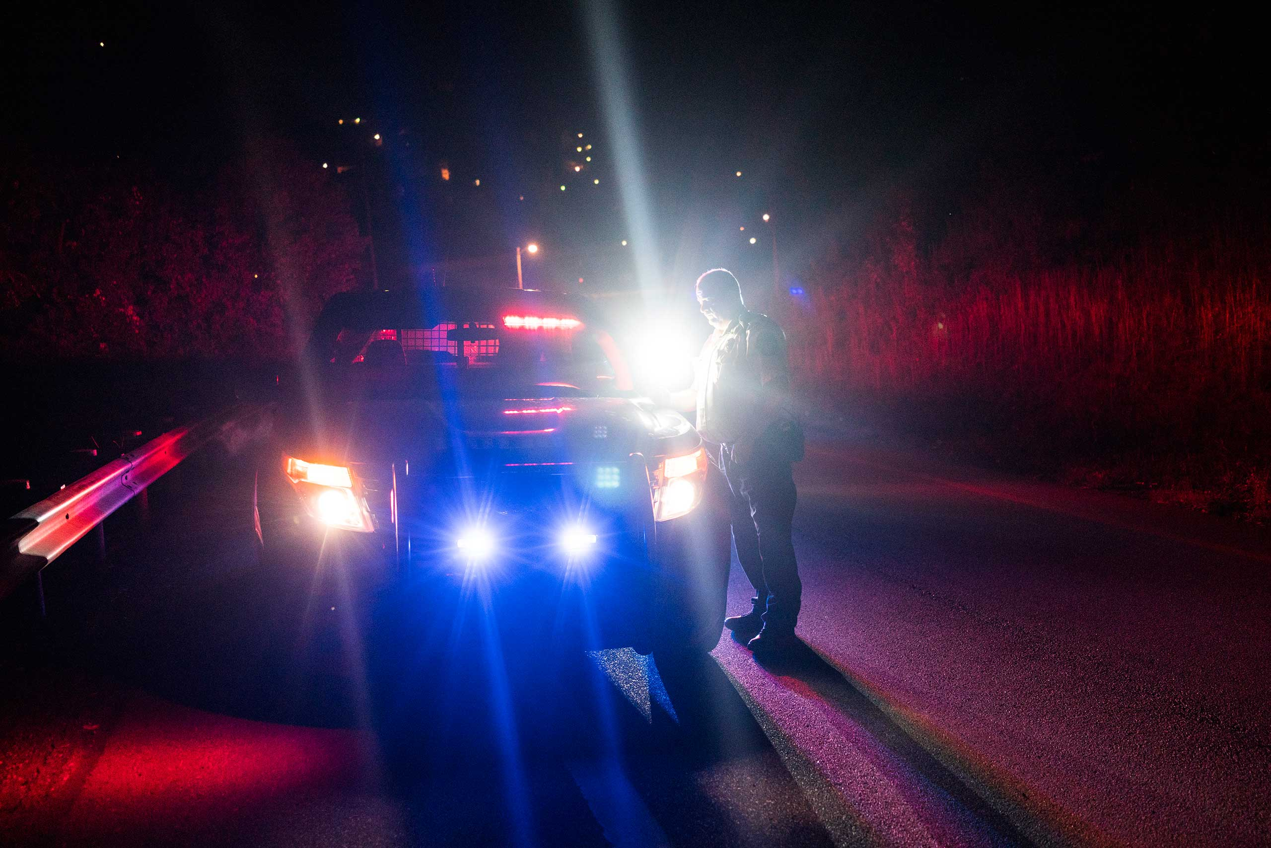 An East Liverpool police officer stands near his vehicle during a possible drug stop on the highway on Oct. 8, 2016. Police said many drug users have a Driver's ID from one state and plates from another since East Liverpool is right on the border between Ohio, Pennsylvania and West Virginia. Drug offensives are much more severe in the latter, so many prefer to be caught and charged in Ohio.