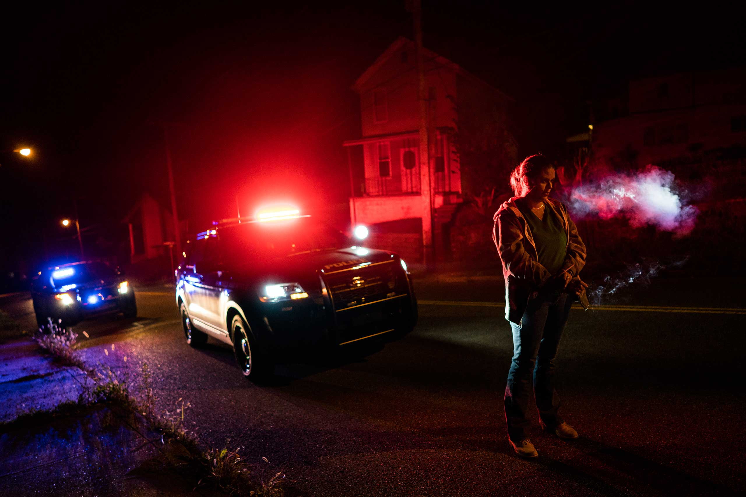 A suspect stopped by police smokes a cigarette, as his car is searched for drugs, in East Liverpool, Ohio, on Oct. 8, 2016.