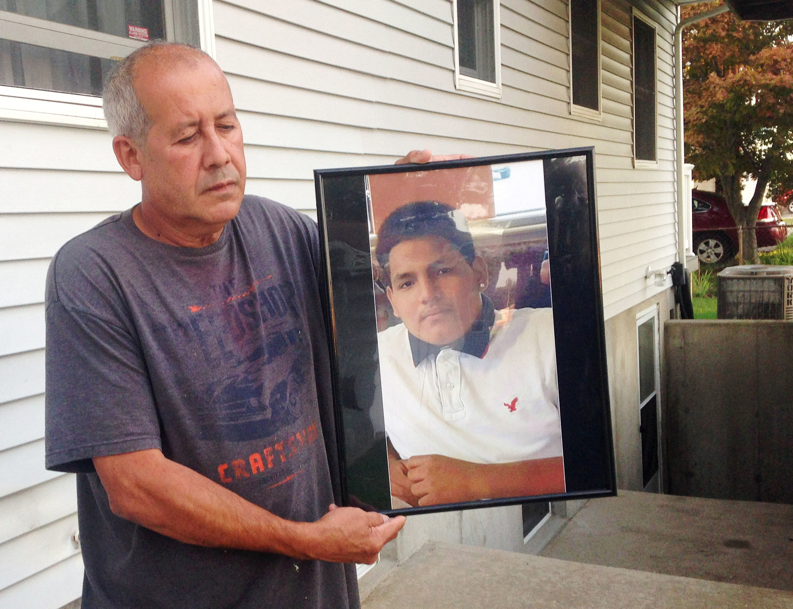 Abraham Chaparro holds a photograph of his murdered stepson, Miguel Garcia-Moran, outside his home in Brentwood, N.Y., on Sept. 27, 2016.