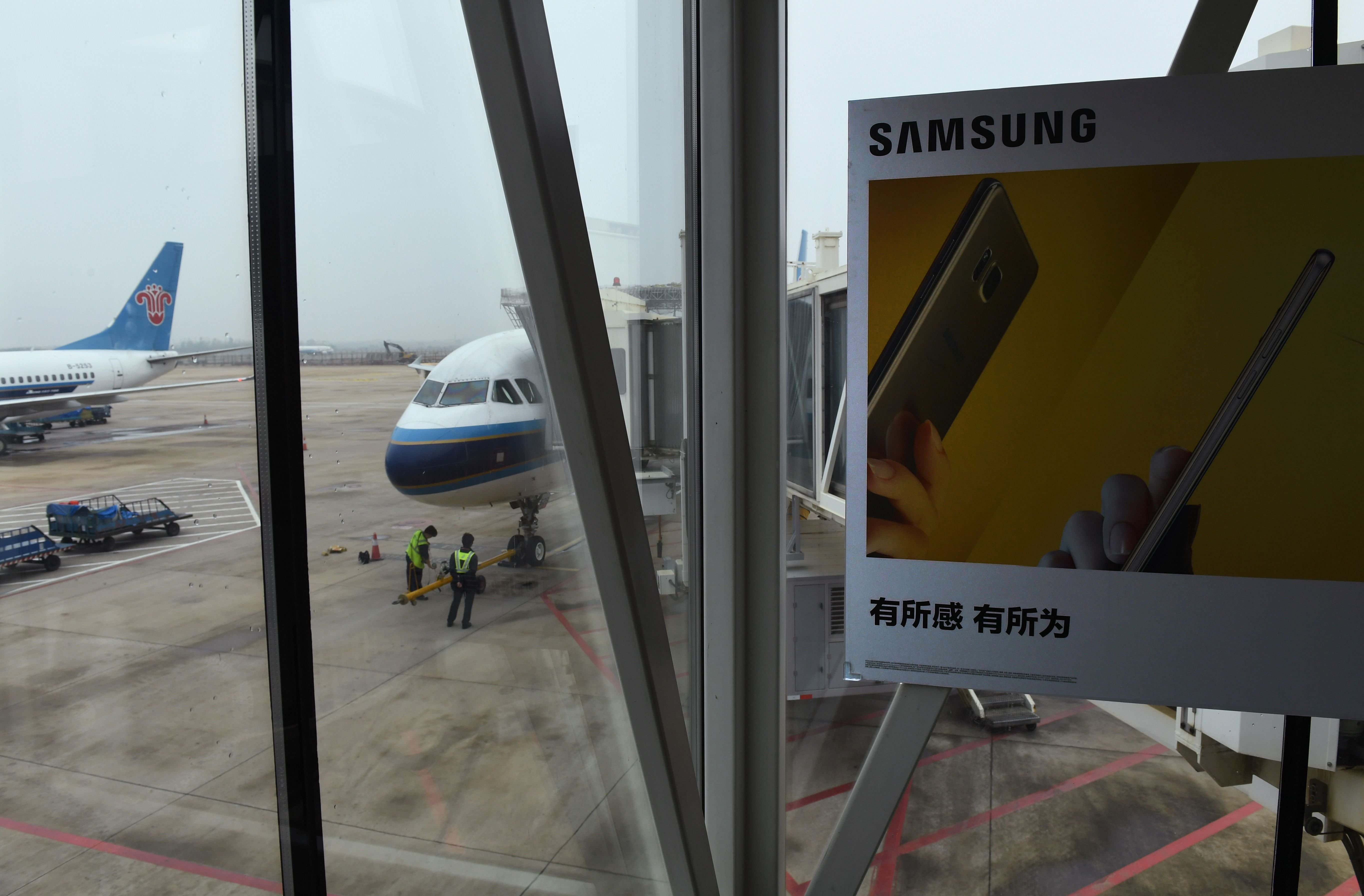 Signs at check-in counters warn passengers not to switch on or charge Note 7 smartphones on the plane and ban them from check-in luggage, following Samsung's recall of Note 7 phones after cases of batteries catching fire were reported in the US, at the Wuhan airport in China, on Oct. 2, 2016.