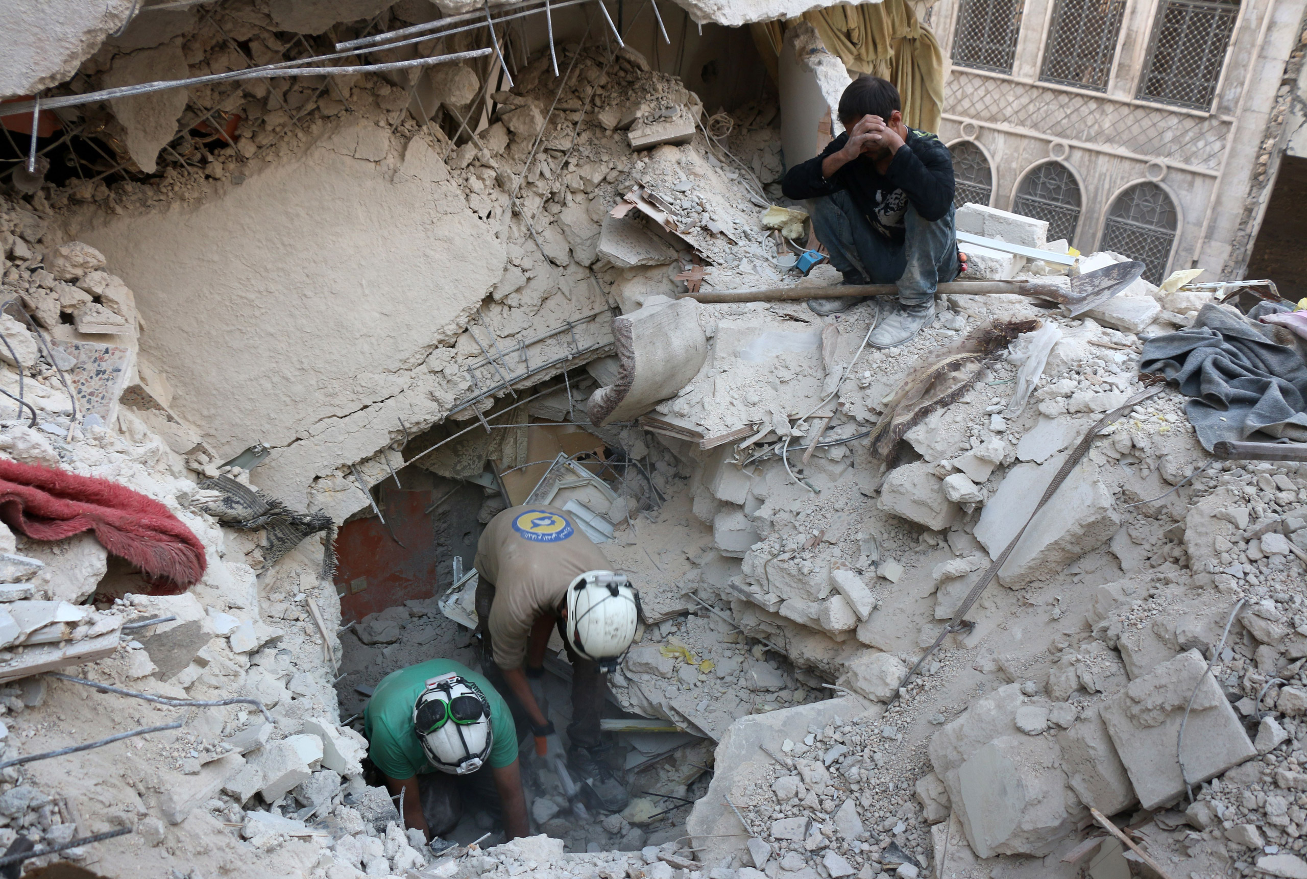 Syrian civil defence volunteers, known as the White Helmets, search for victims amid the rubble of destroyed buildings following a government forces air strike on the rebel-held neighborhood of Bustan al-Basha in Aleppo, on Oct. 4, 2016.