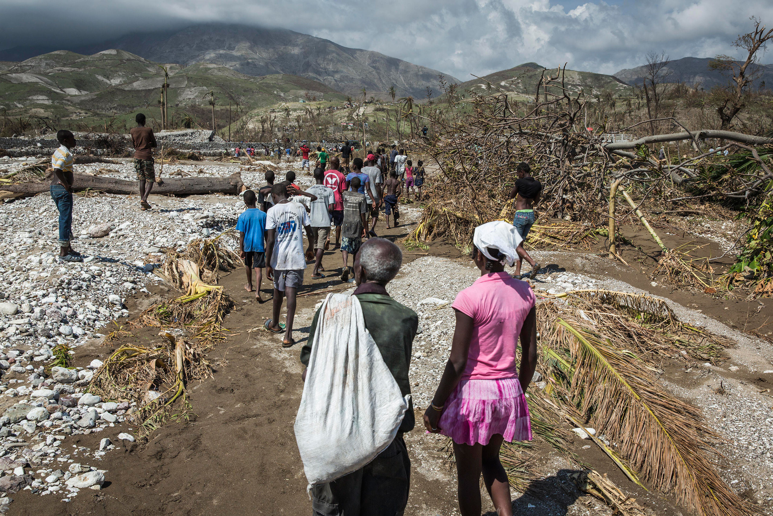 People walk along a path to the river in order to cross through the water on foot as the bridge has collapsed in Roche-a-Bateau, southwestern Haiti, on Oct. 8, 2016. Many Haitians originally from the south of the country are returning home to visit family and help in the recovery from the impact of Hurricane Matthew.