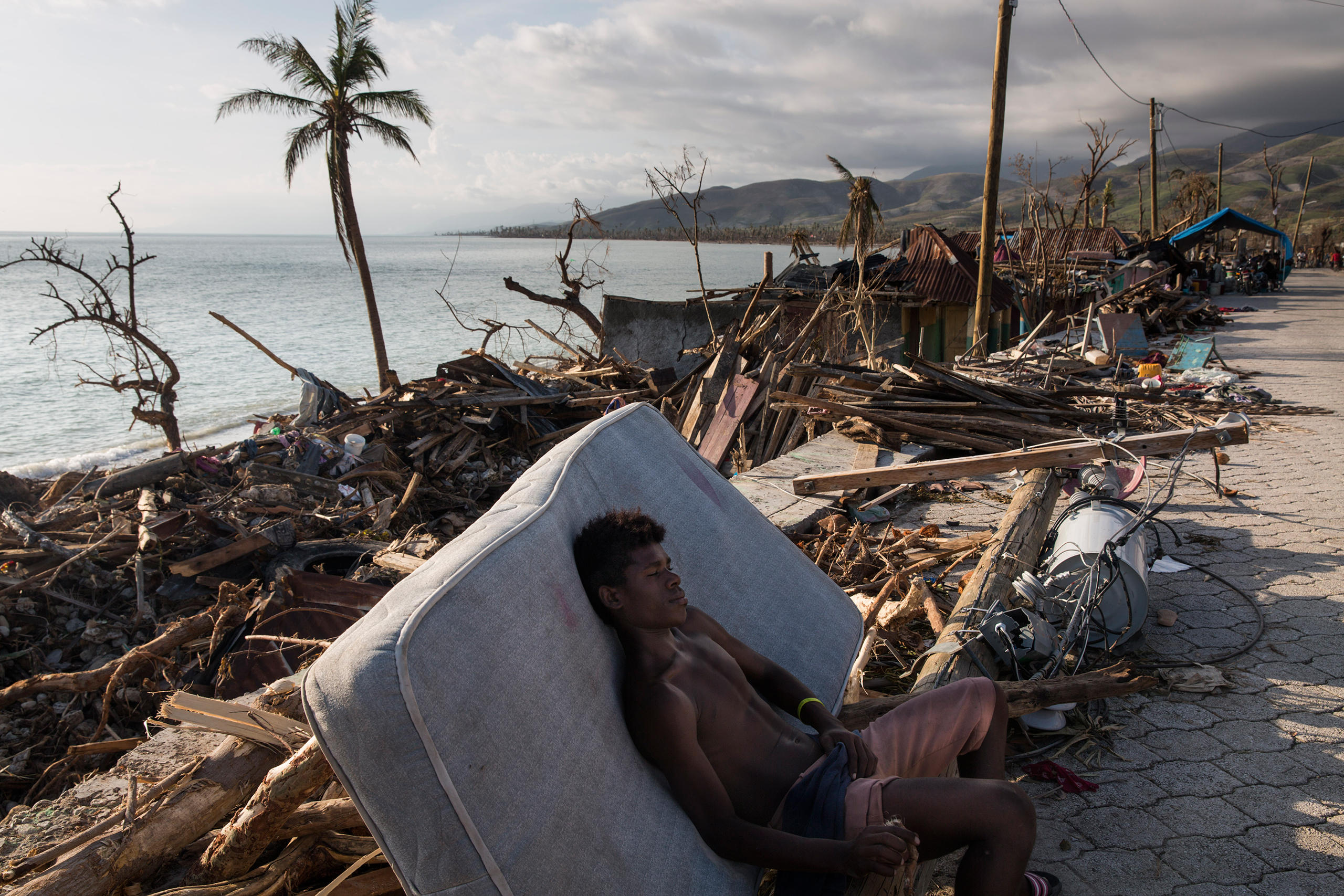 A teenager rests on the side of the road in a devastated area near Port Salut, southwestern Haiti, on Oct. 8, 2016.