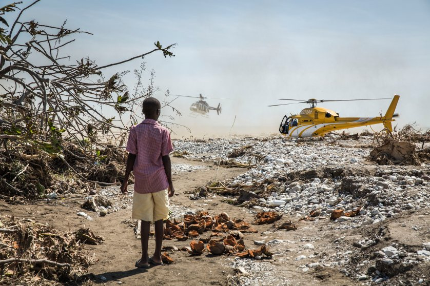 A young boy watches helicopters carrying politicians to the worst hit areas land in Roche-a-Bateau, southwestern Haiti, on Oct. 8, 2016.