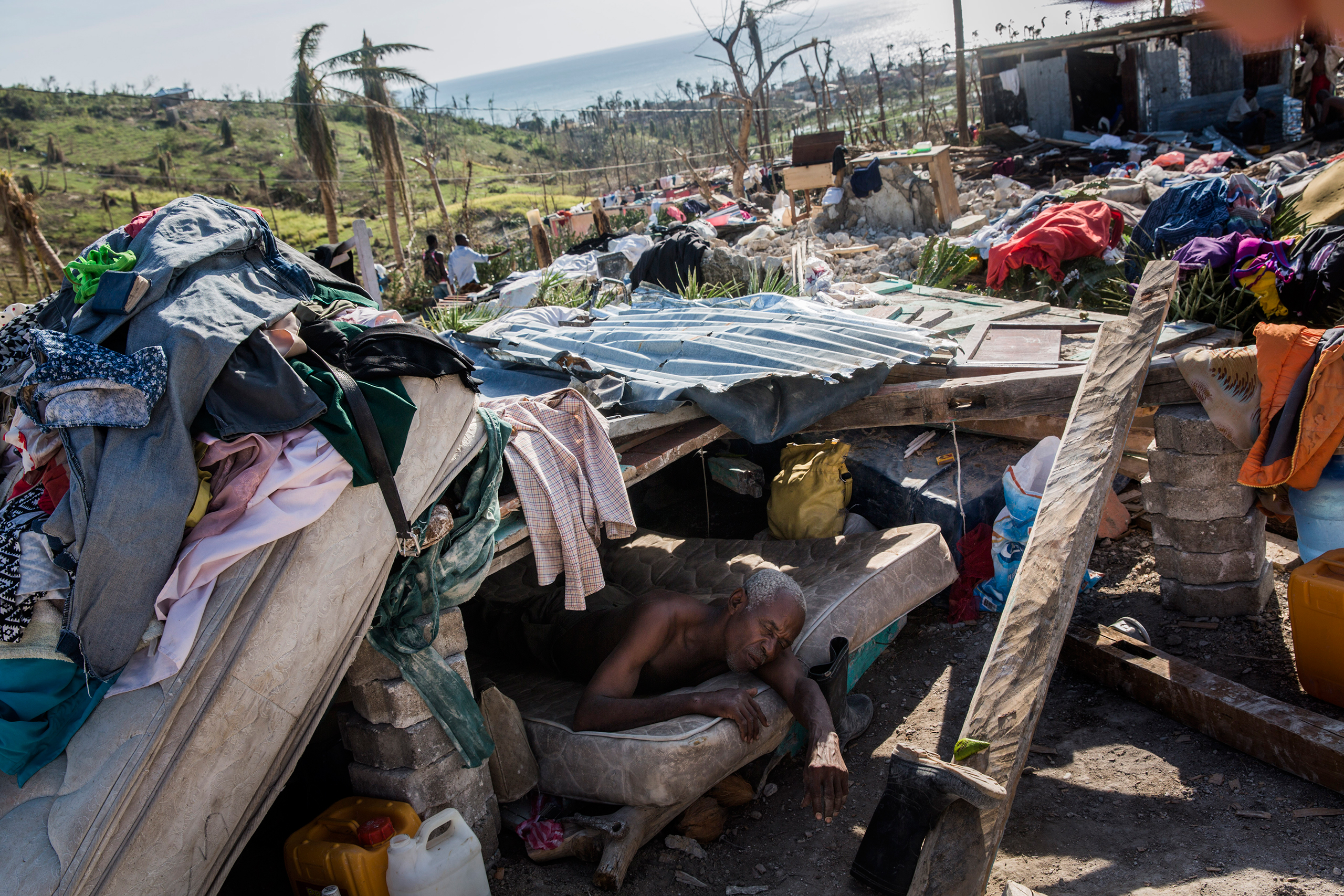 A man who is too ill to walk rests in a makeshift shelter on the site of his destroyed home in Roche-a-Bateau, southwestern Haiti, on Oct. 8, 2016.