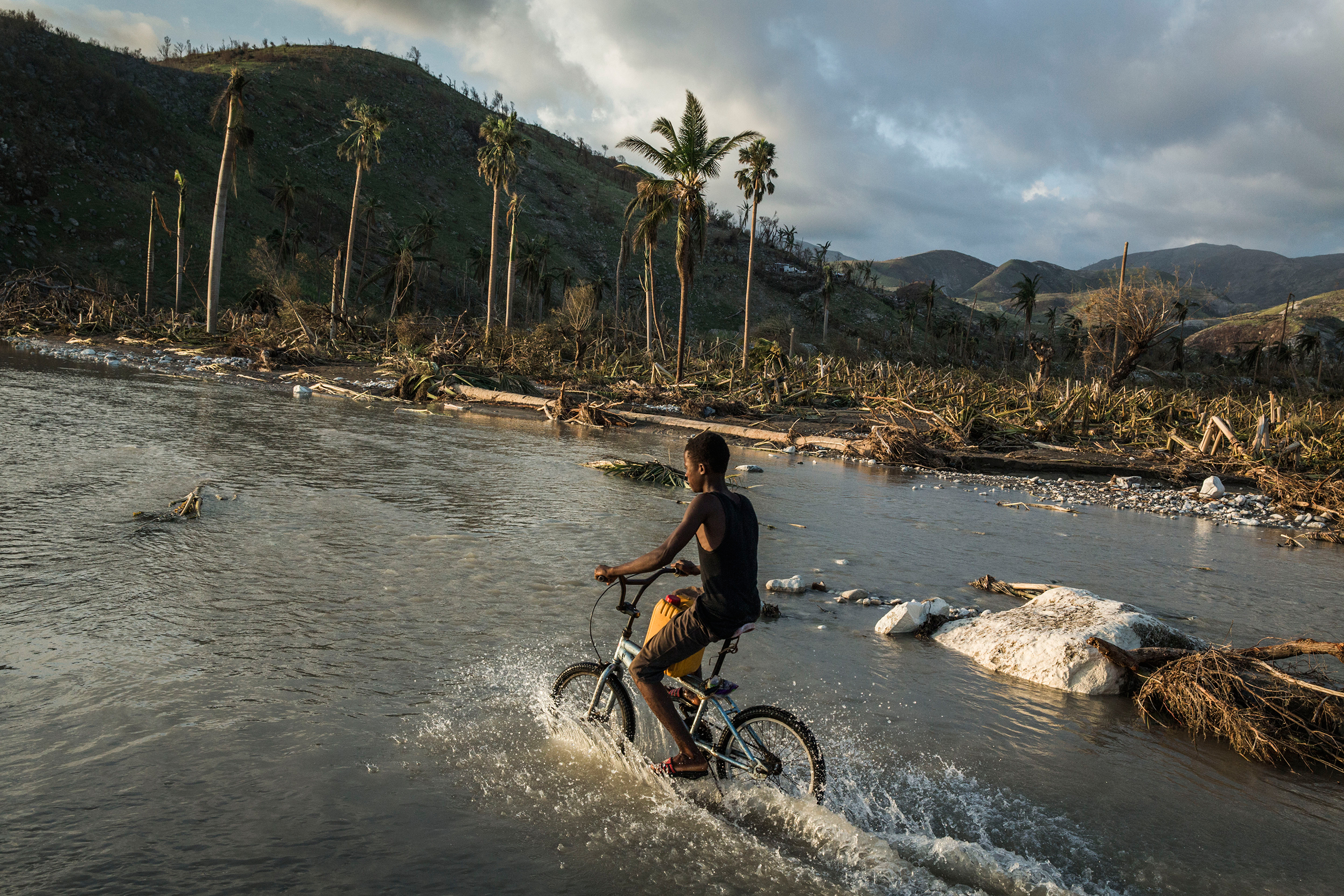A boy rides his bicycle along a flooded road in a devastated area near Port Salut, in southwestern Haiti, on Oct. 8, 2016.