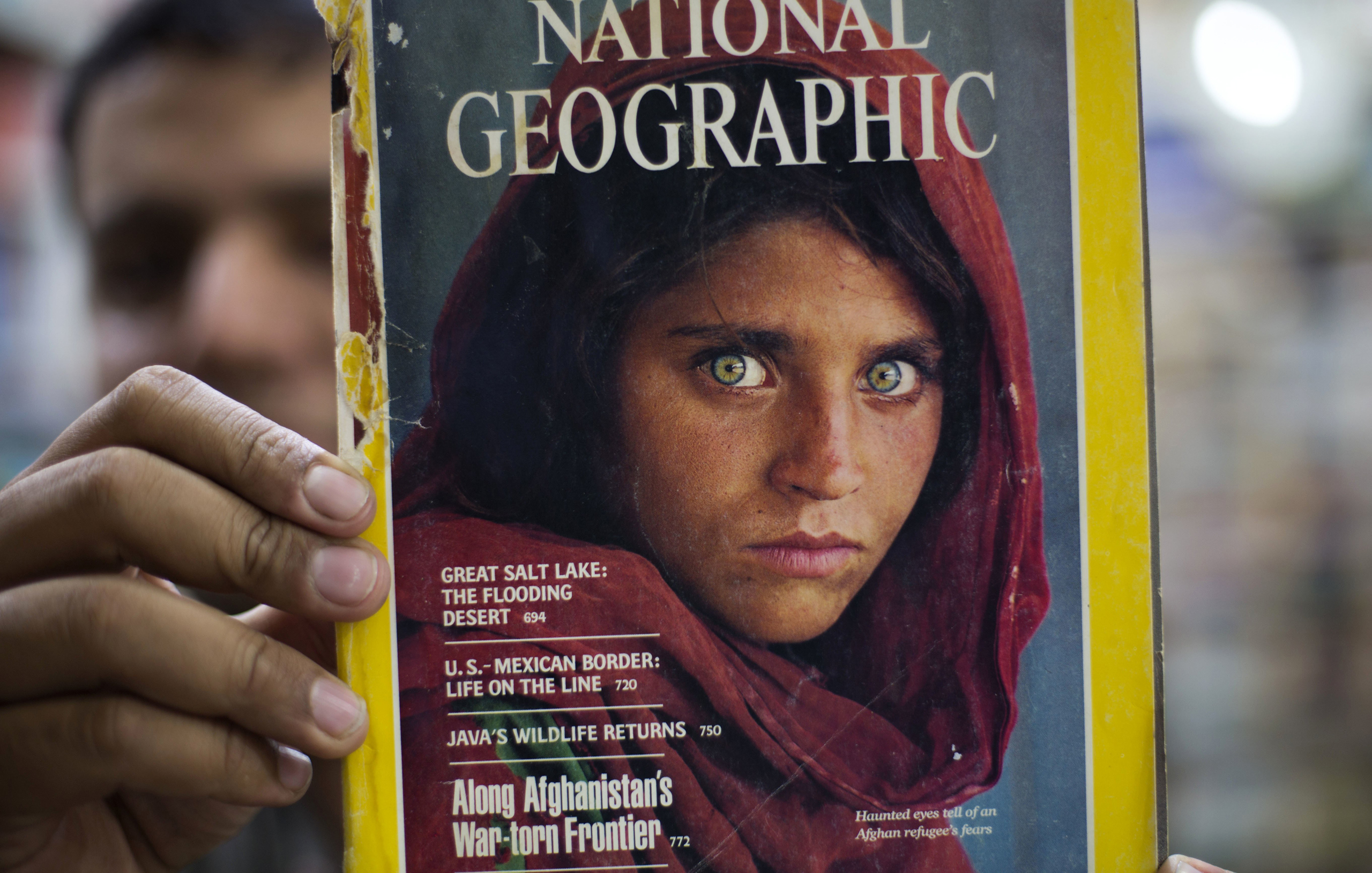 Pakistan's Inam Khan, owner of a book shop shows a copy of a magazine  with the photograph of Afghan refugee woman Sharbat Gulla, from his rare collection in Islamabad, Pakistan, on, Oct. 26, 2016. A Pakistani investigator says the police have arrested National Geographic's famed green-eyed 'Afghan Girl' for having a fake Pakistani identity card.