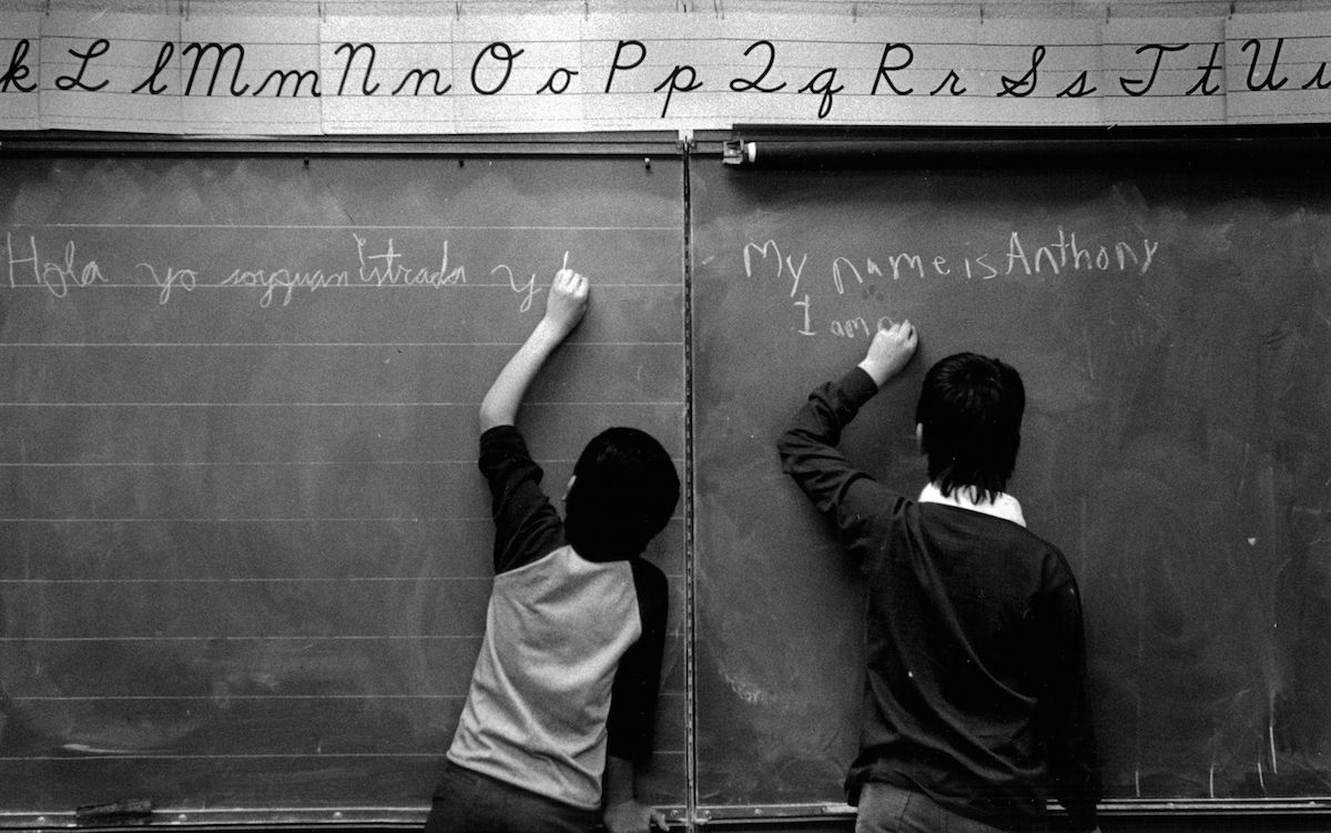 Scene from a bilingual classroom in Denver in 1987: Juan Estrada (11) and Anthony Vasquez (9) write an introduction to themselves on the blackboard in the language that each of them knows best.
