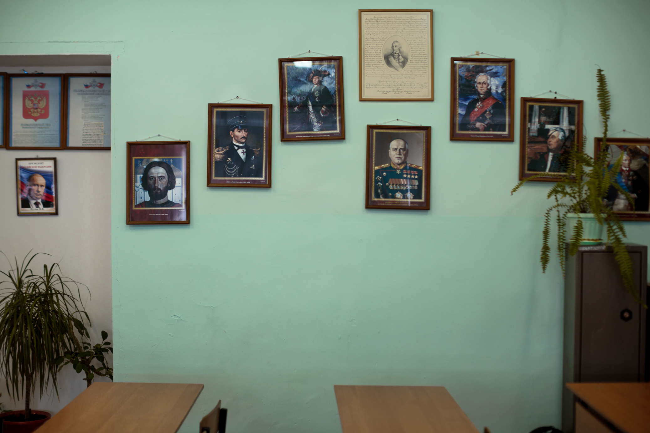 A classroom wall decorated with legacies from Russian history, starting with Vladimir Putin on the far left.