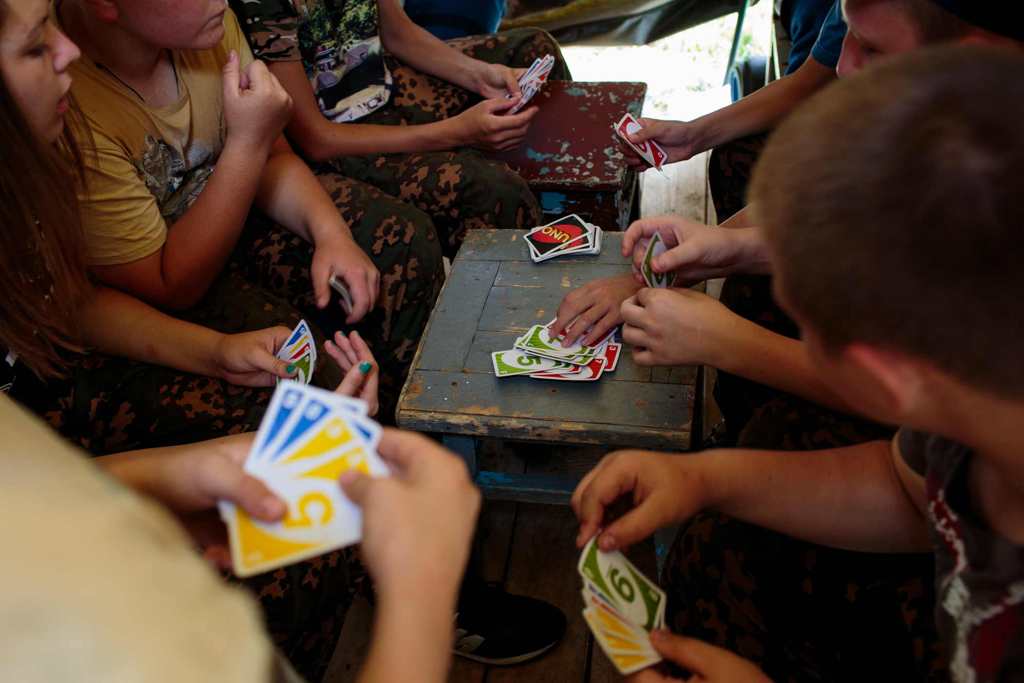 Campers play a game of UNO in their tent between drills.