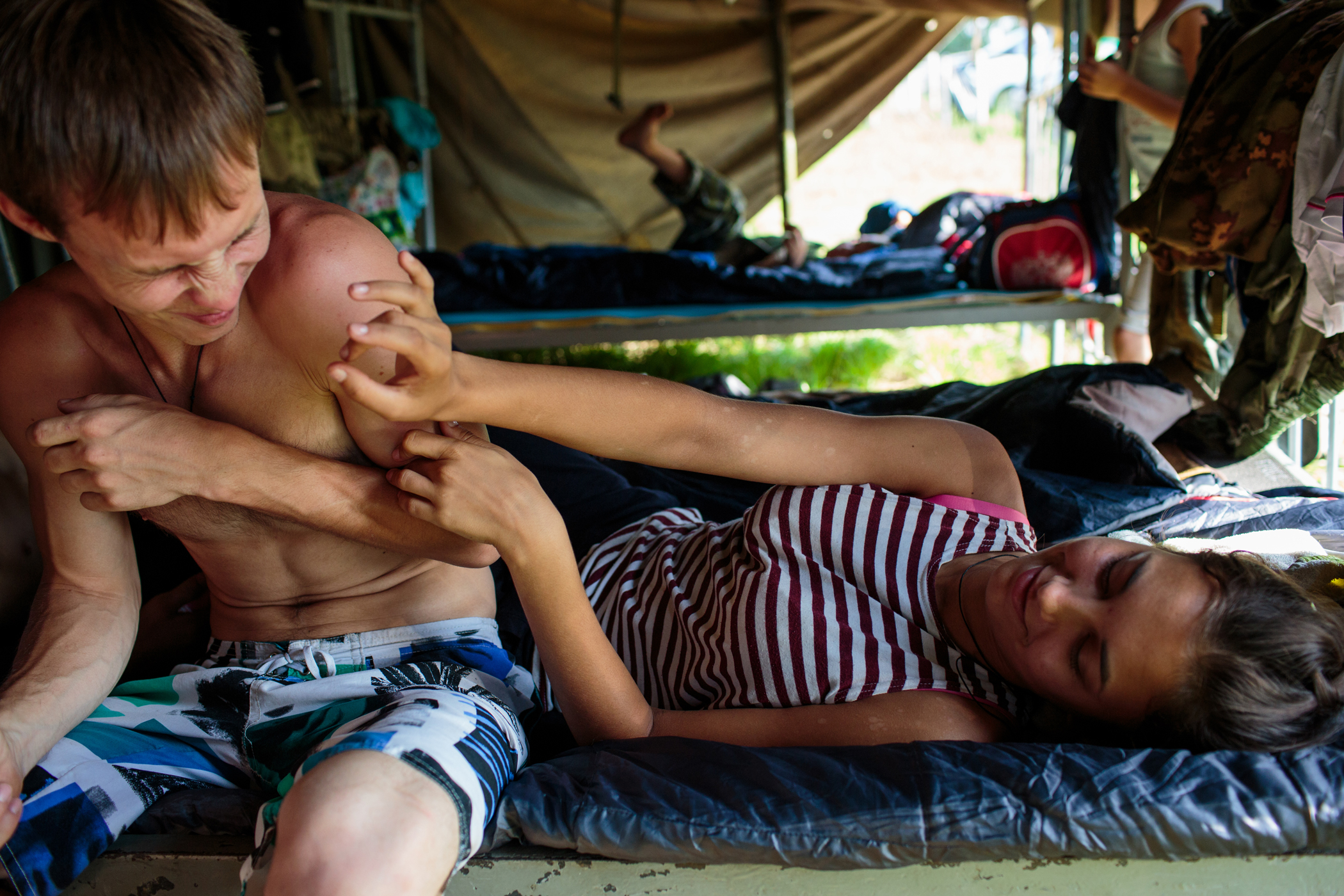 Oleg Shaula and his girlfriend Nadya Gross from Stavropol relax in a tent during the first day of the hand-to-hand combat competition at the  Orthodox Warrior  camp.