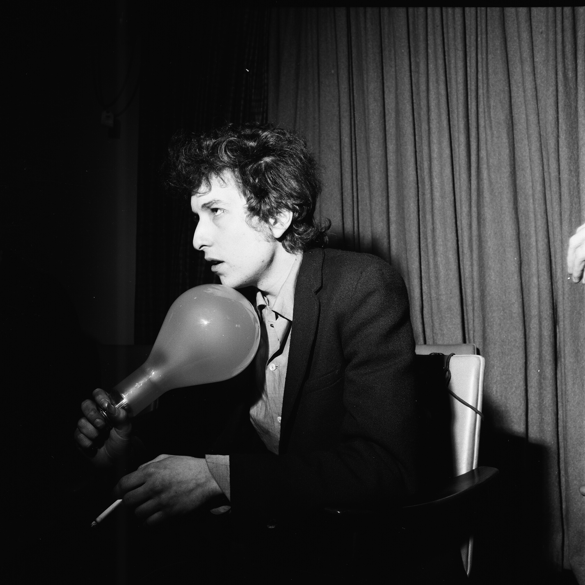 Bob Dylan holding a large light bulb at a press conference, London, 1965.