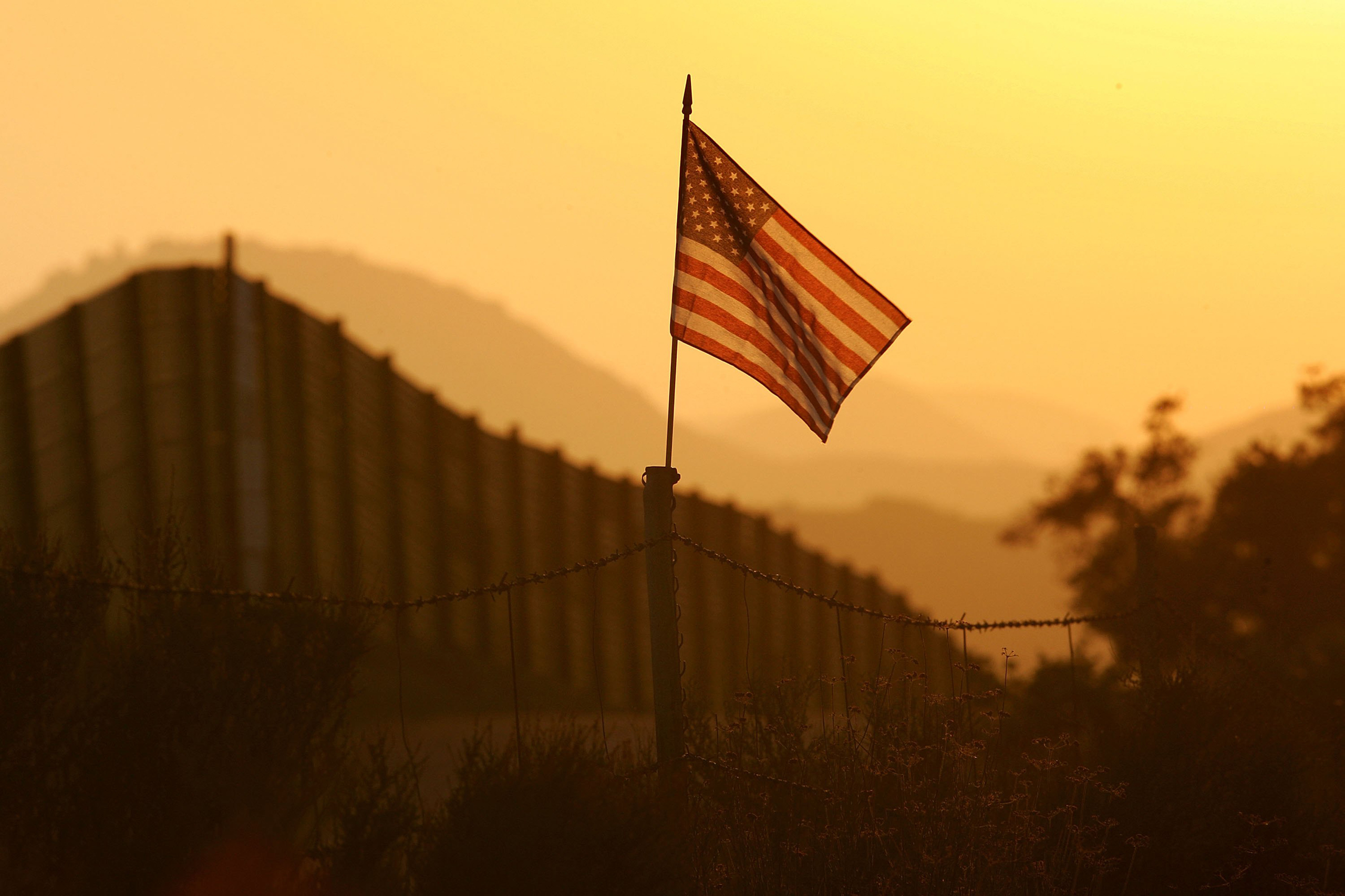 A U.S. flag put up by activists who oppose illegal immigration flies near the US-Mexico border fence near Campo, California, on Oct. 8, 2006.