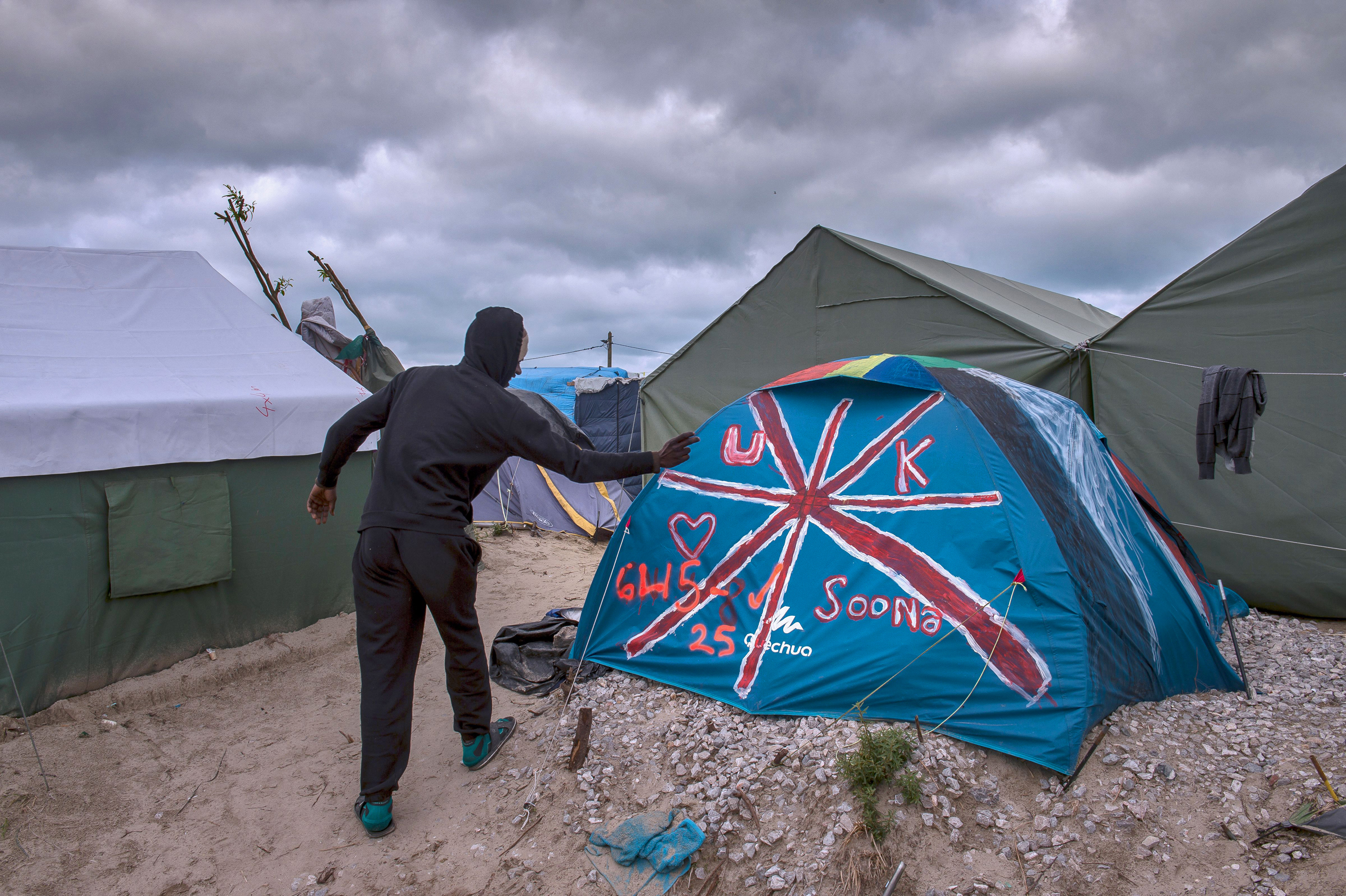 A Sudanese man stands near a tent painted with the British flag at the  Jungle  migrant camp in Calais on Oct. 12, 2016.