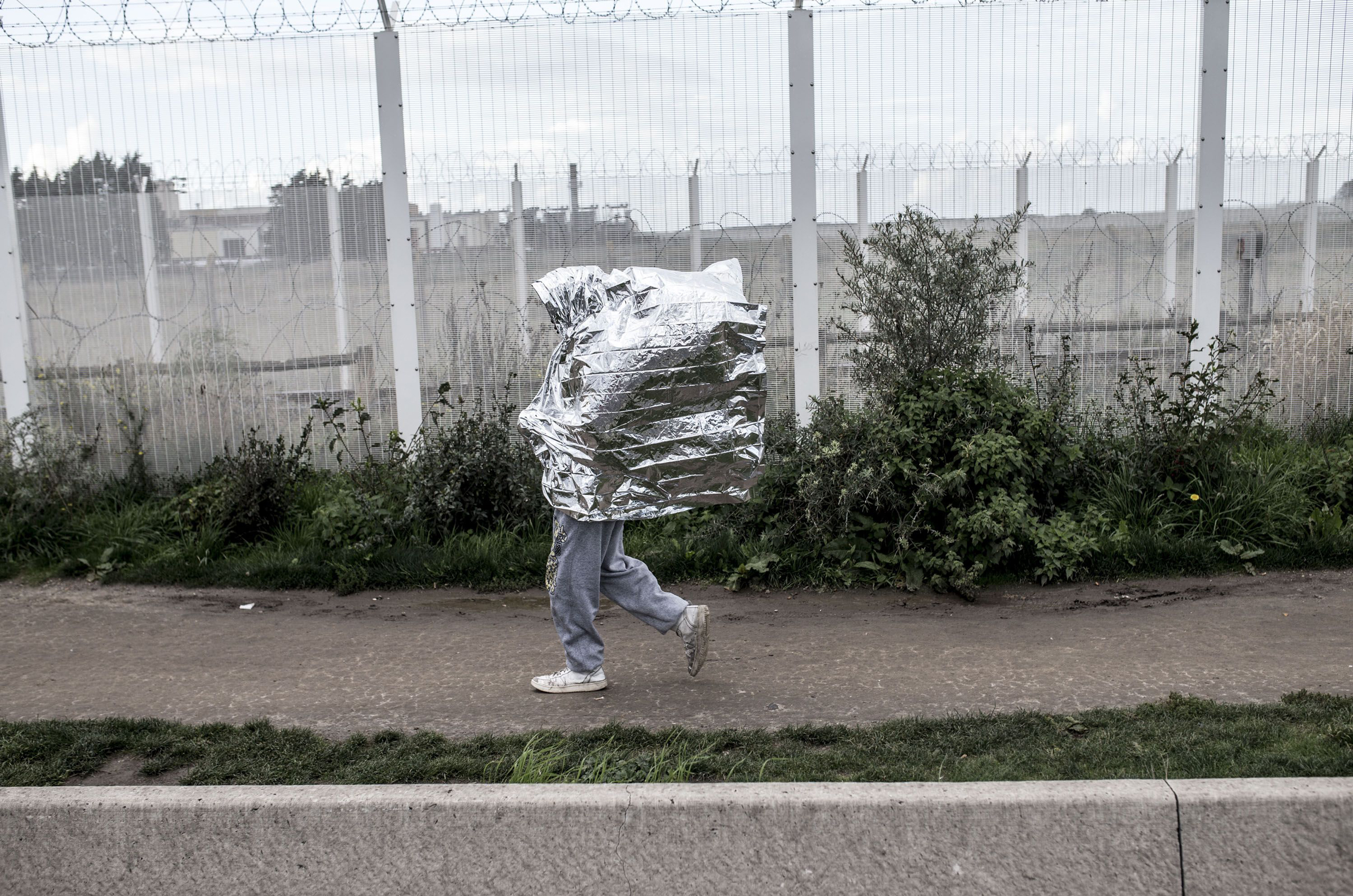 A resident of the refugee camp called 'The Jungle' walking with a survival blanket in Calais, France, on Oct. 17, 2016.