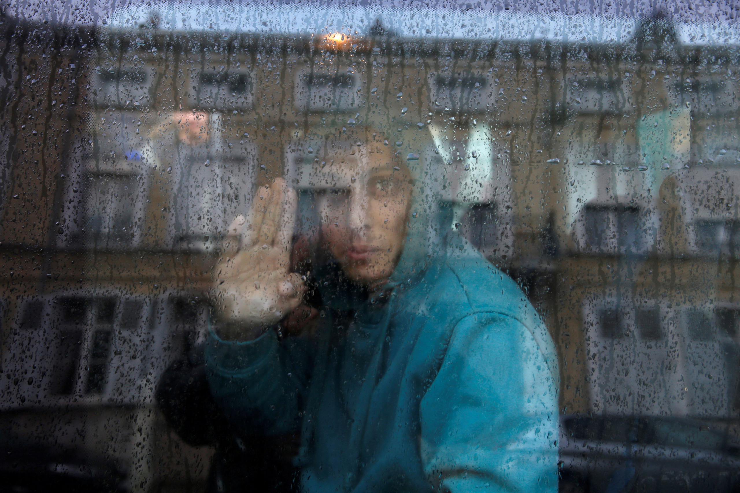 An Afghan adolescent migrant waves from a van as he departs with six others for Britain from the emergency shelter for minors in Saint Omer, France, on Oct. 18, 2016.